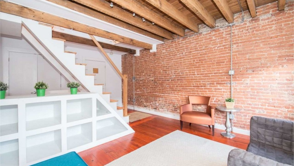 &nbsp;<br>A living room with exposed beams and colorful orange and blue furniture.