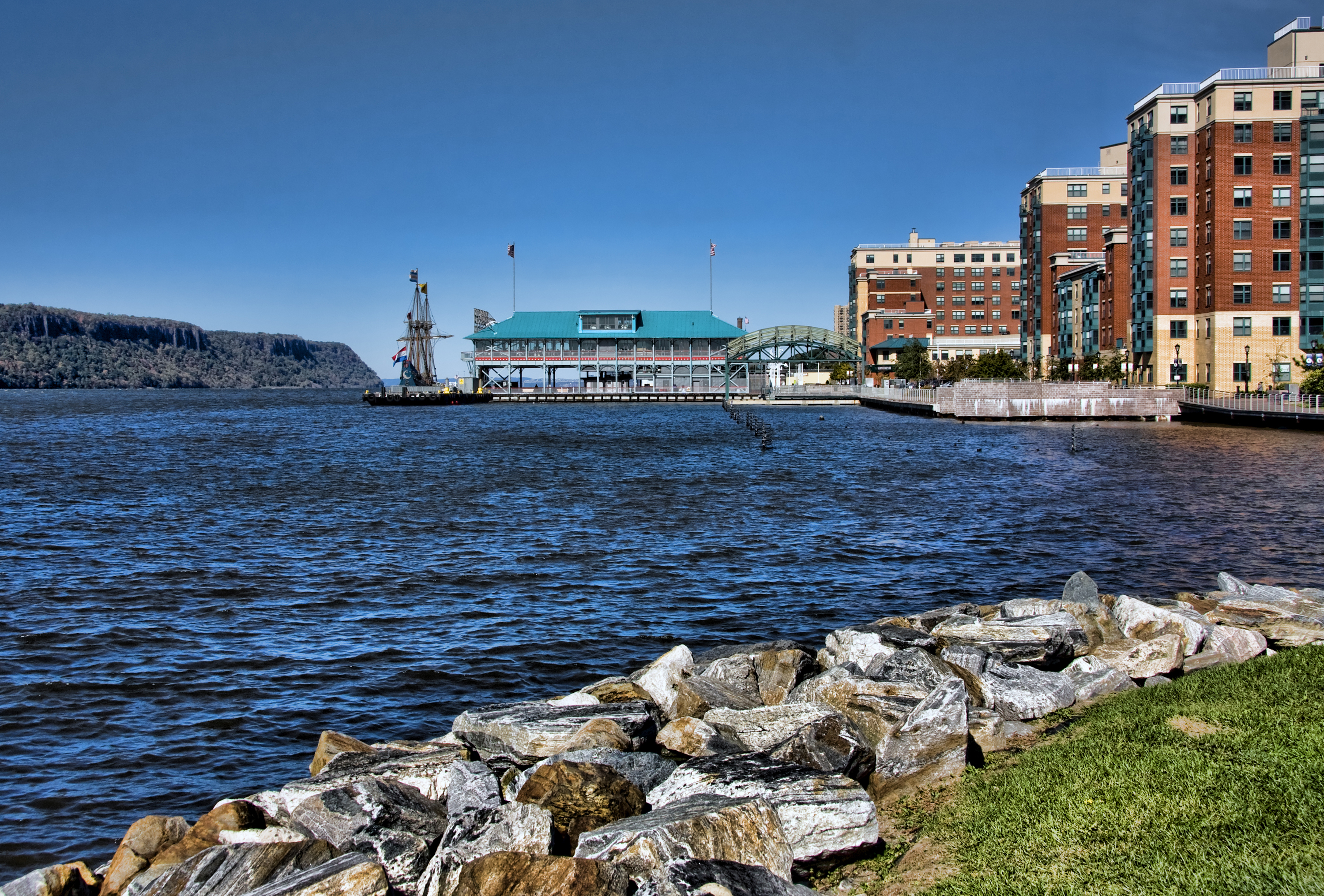 A waterfront with rocks and green grass. The water is blue and there are buildings in the distance.