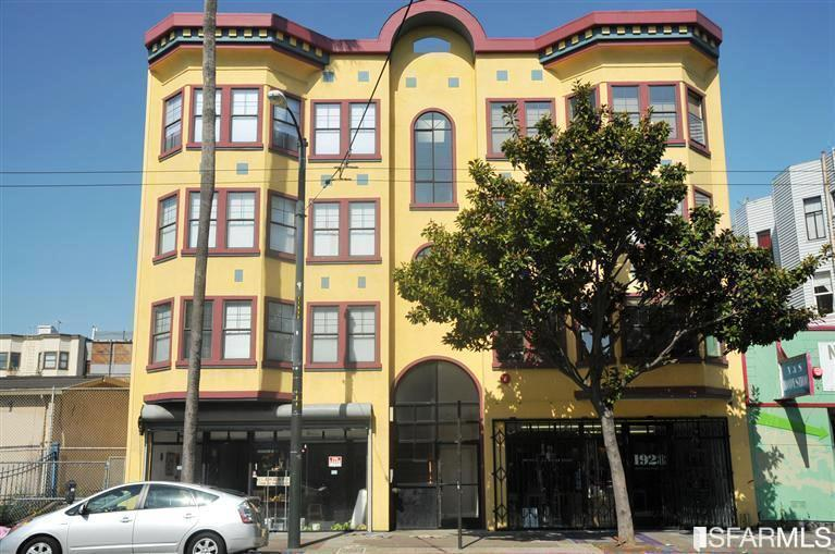 The yellow facade of a four story building on Mission Street.
