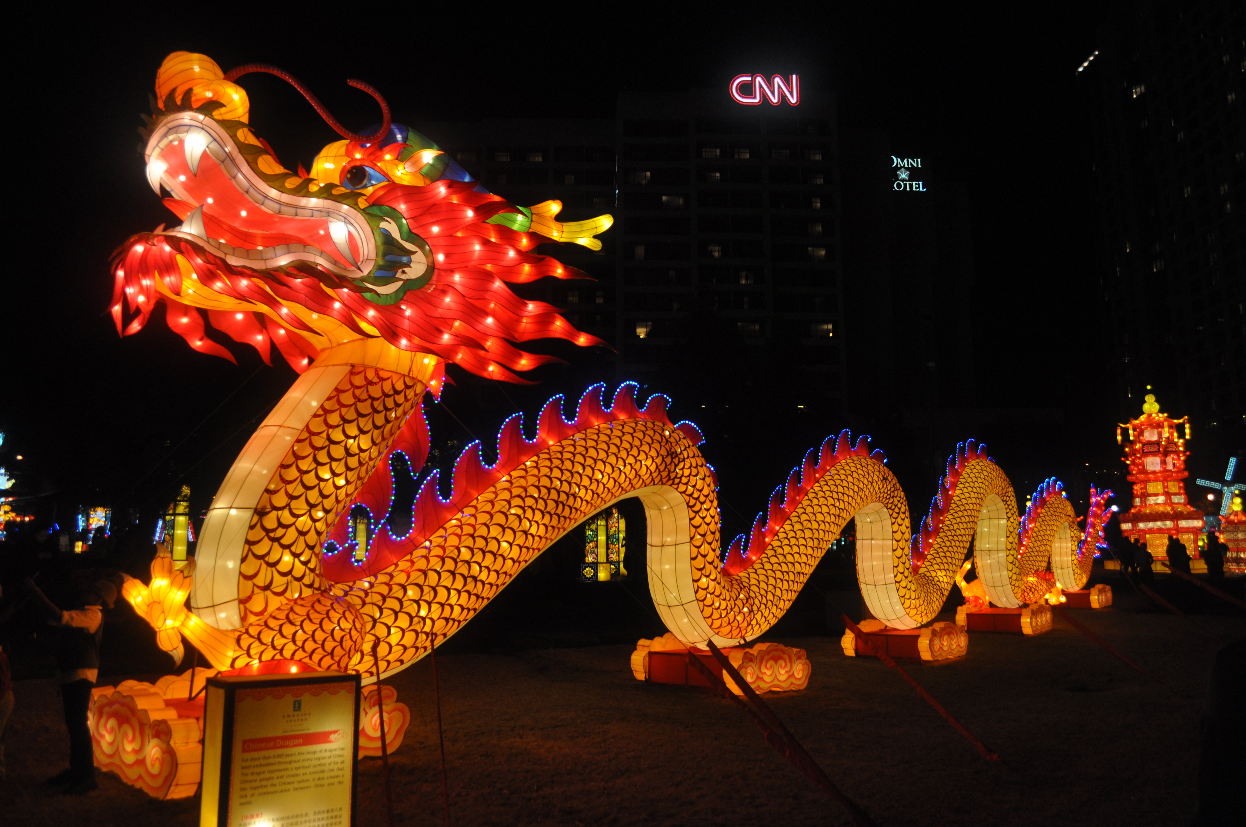 A long, red, yellow, and blue illuminated dragon stretches through Centennial Olympic Park under the CNN Center sign.