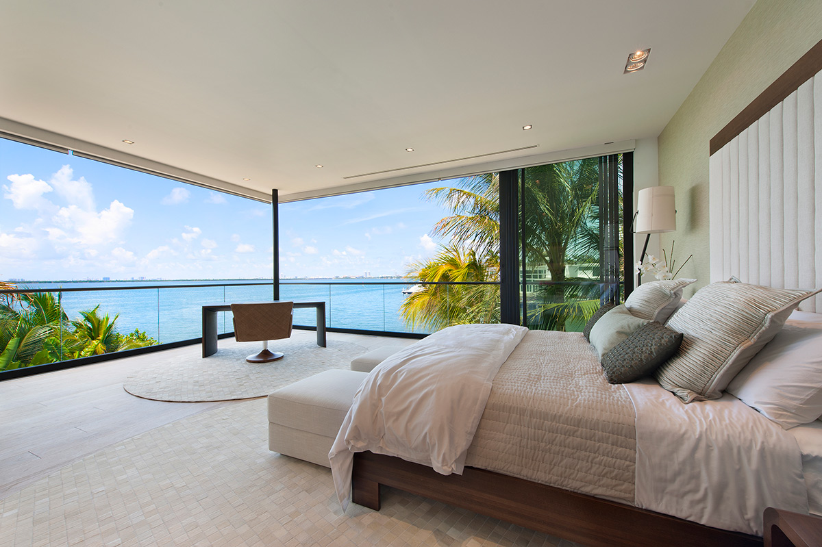 A gorgeous master bedroom with collapsing doors showing Biscayne Bay