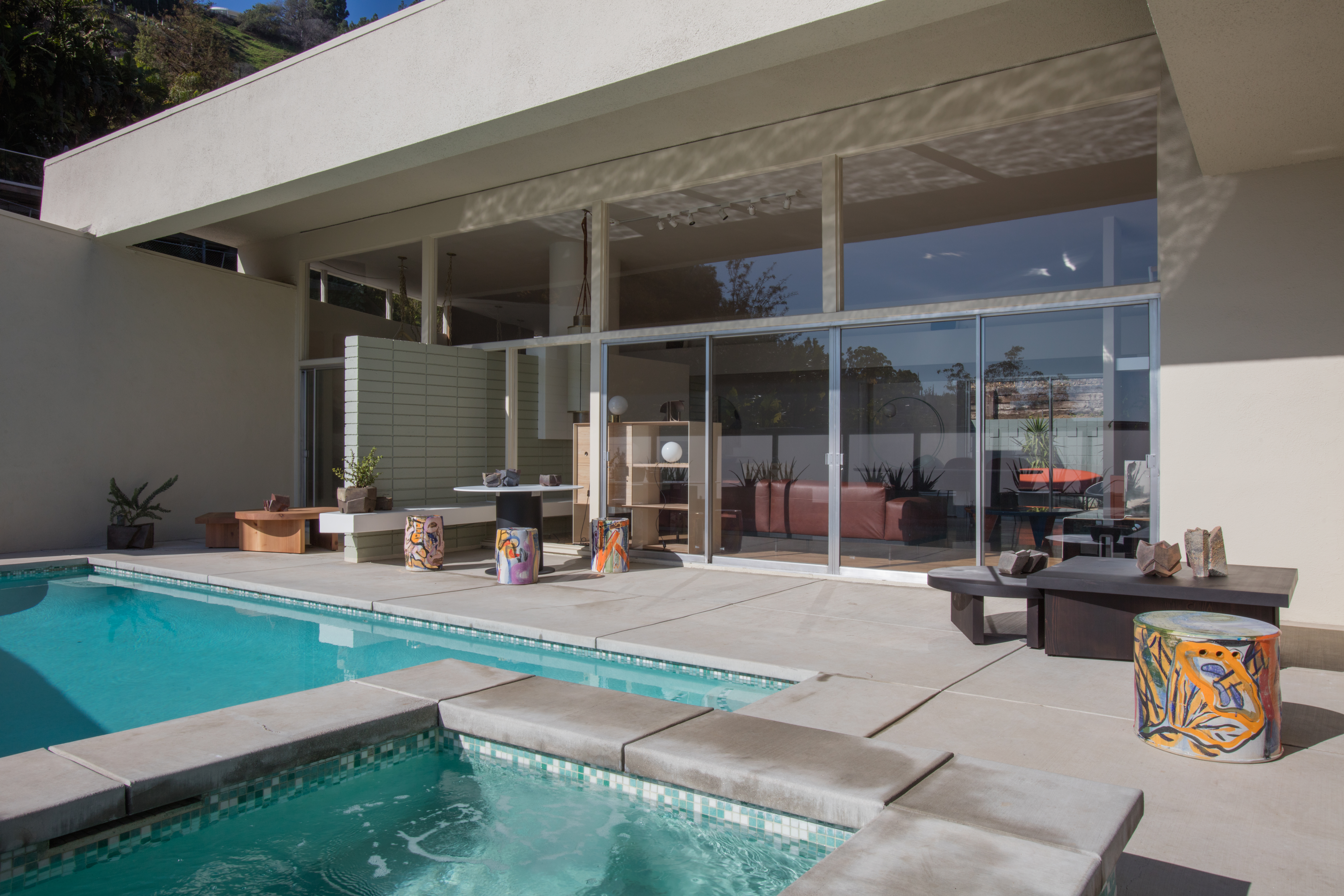 Exterior shot of low-slung white frame house with wall of windows off the living room looking out onto a pool, with various furniture and design objects populating the space both inside and out.