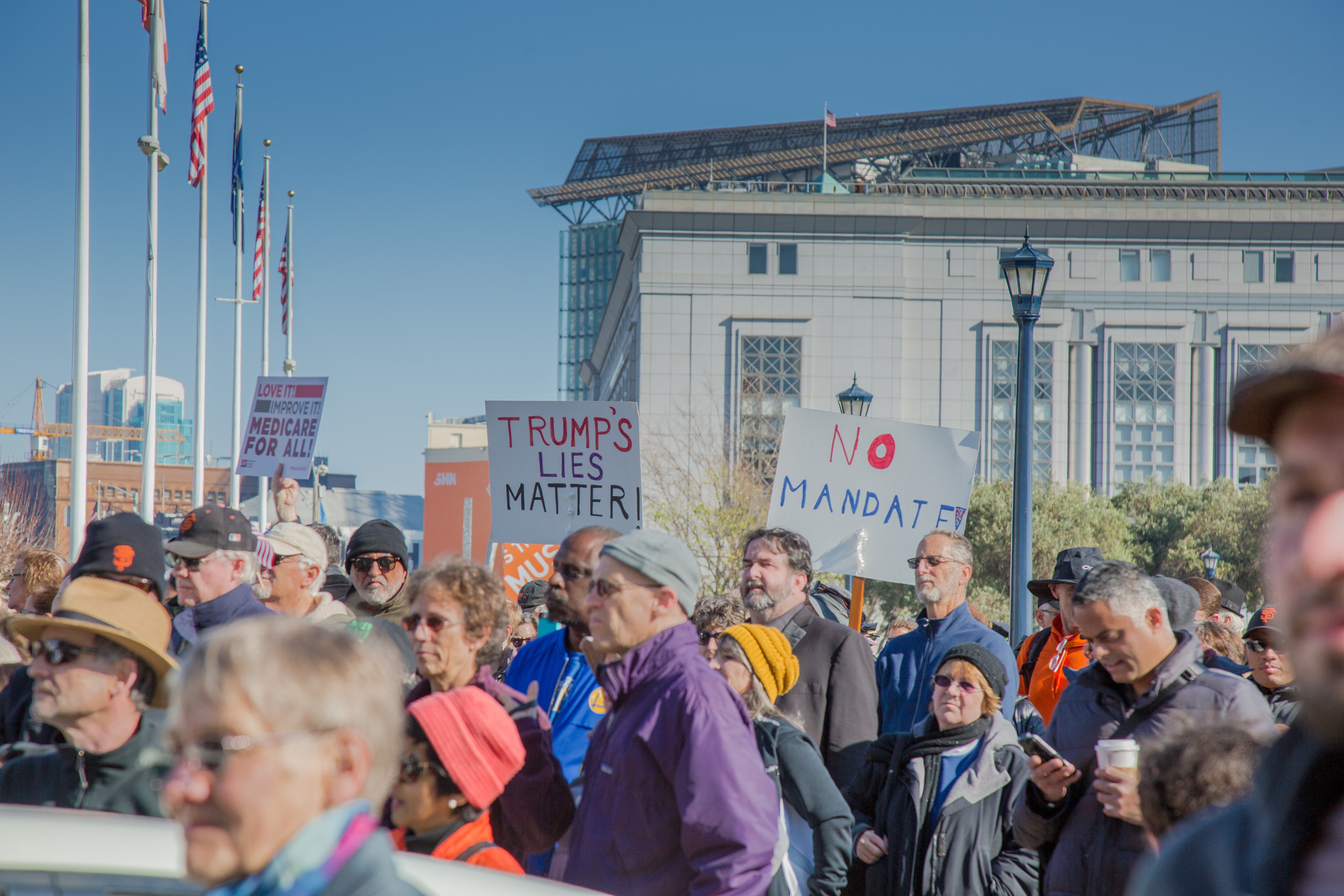 A person holds a sign as people assemble during a Healthcare rally held in front of city hall in downtown San Francisco.