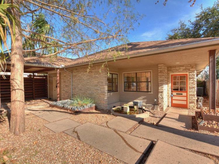 One-story small family house built in 1951, light tan brick, orange door, carport