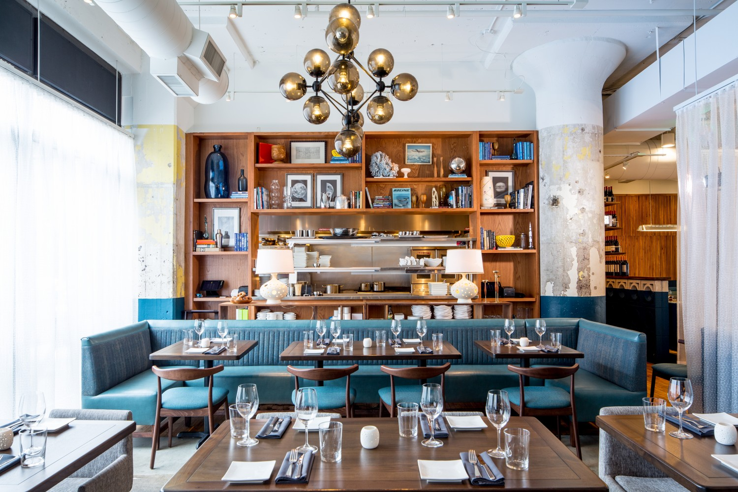 A tall bookshelf filled with nick-nacks fills a wall behind a mid-century inspired dining room at Mercury in Ponce City Market.