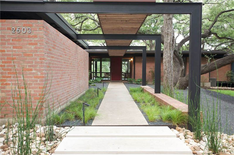 Exterior entrance to a midcentury/international style house, long walkway with wooden covering mirroring sidewalk above, red brick one-story, flat-roofed house to left and continued in back, front door and windows that enable view through house, tree over