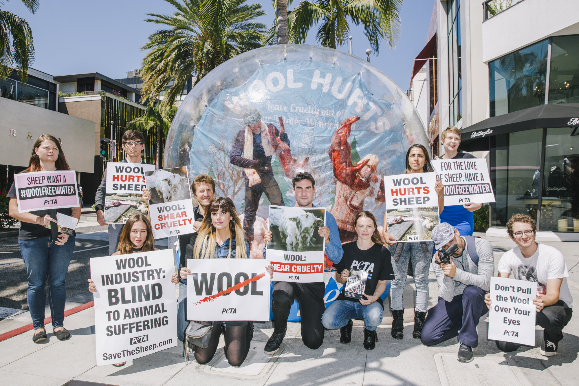 PETA staffers stand outside with signs at a wool protest in Los Angeles. Two people beating up fake bloody sheep are inside a giant inflatable snow globe behind them.