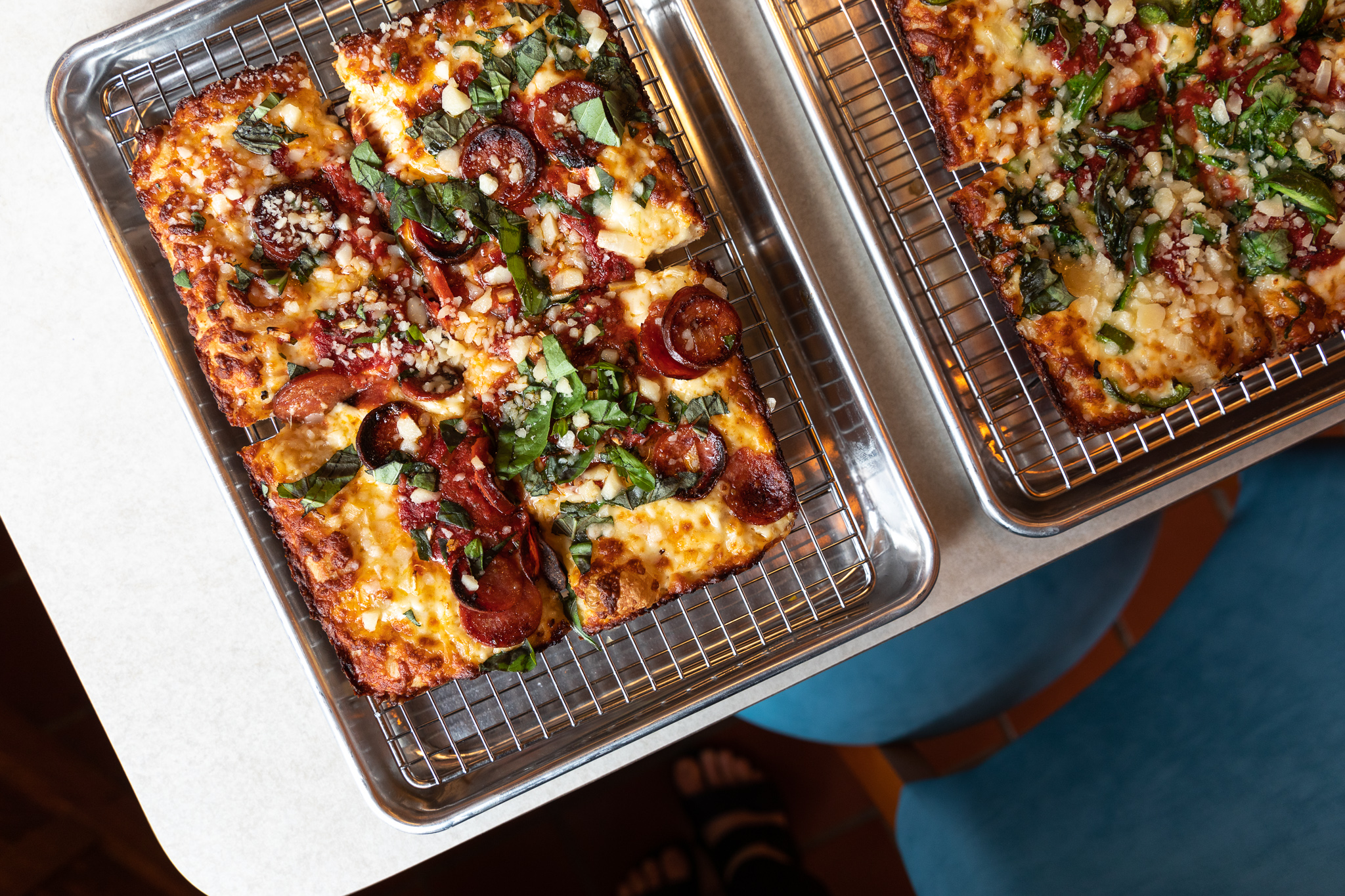 A rectangular pizza cut into four quarters with lots of fresh basil, crumbled cheese, and thick-sliced pepperoni on a cooling rack inside a metal tray.
