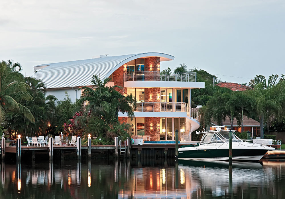 A canalfront home in Fort Lauderdale with three stories and a unique curved roof