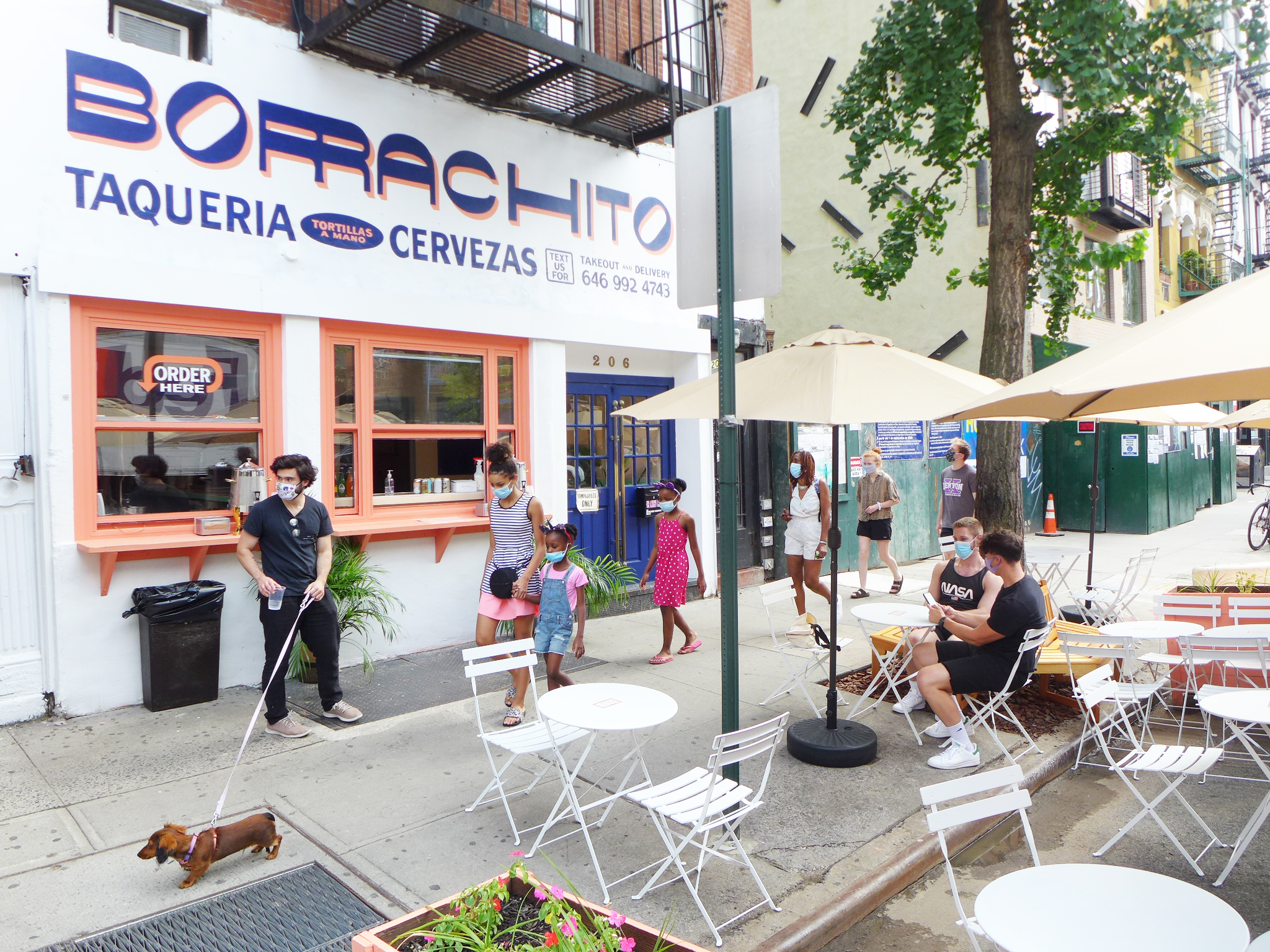 Bright white storefront with stenciled name, pedestrians pass by one with a dachsund, outdoor tables in foreground.