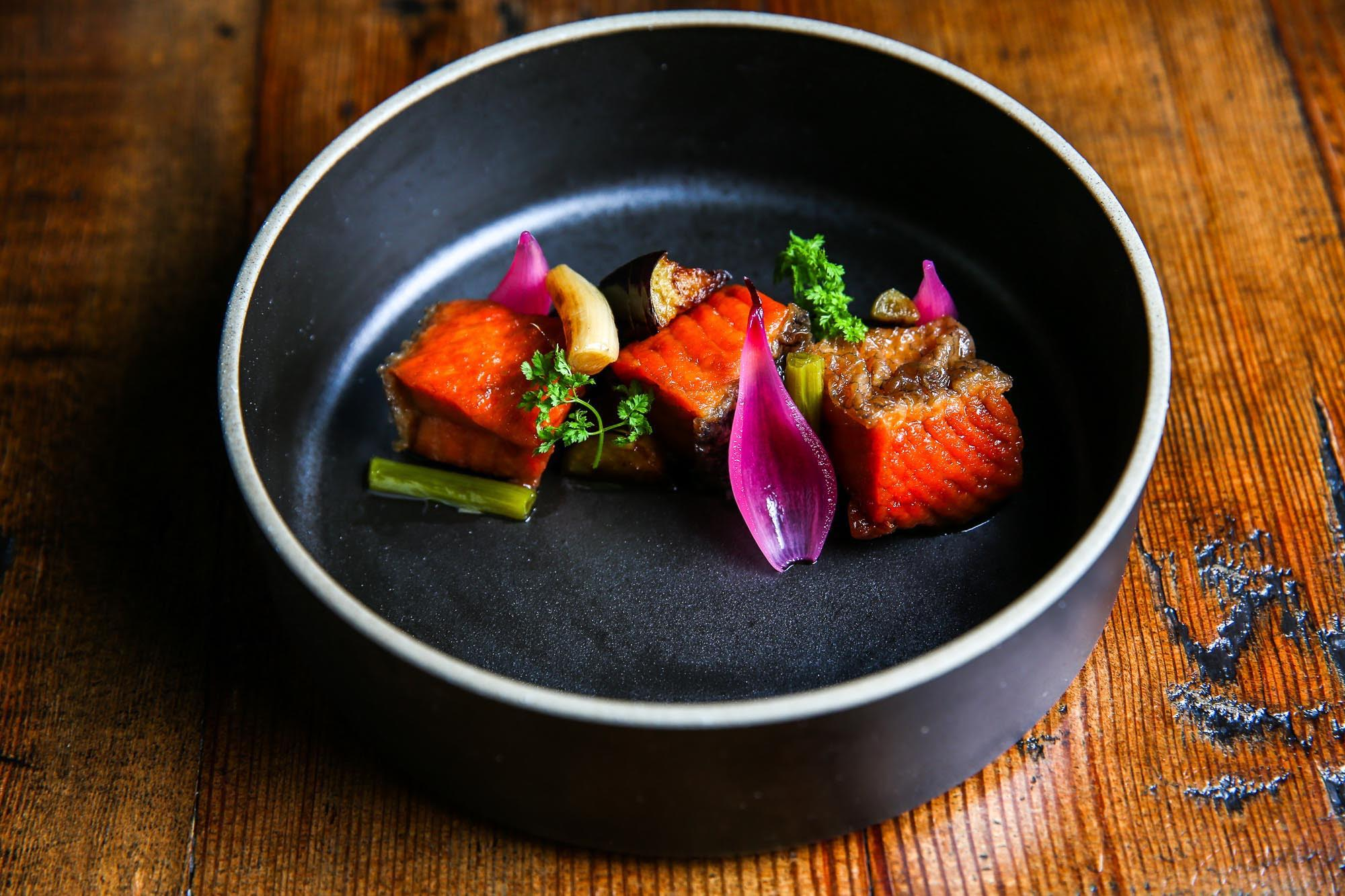 A plate of salmon chunks fried and marinated in a soy vinaigrette with eggplants and pickled red onion.