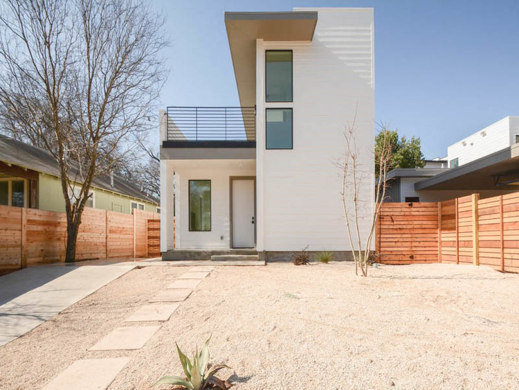 New contemporary house with two stories on right side and one story with roof deck on letf. White, modern design, cedar fences on sides, gravel front yard