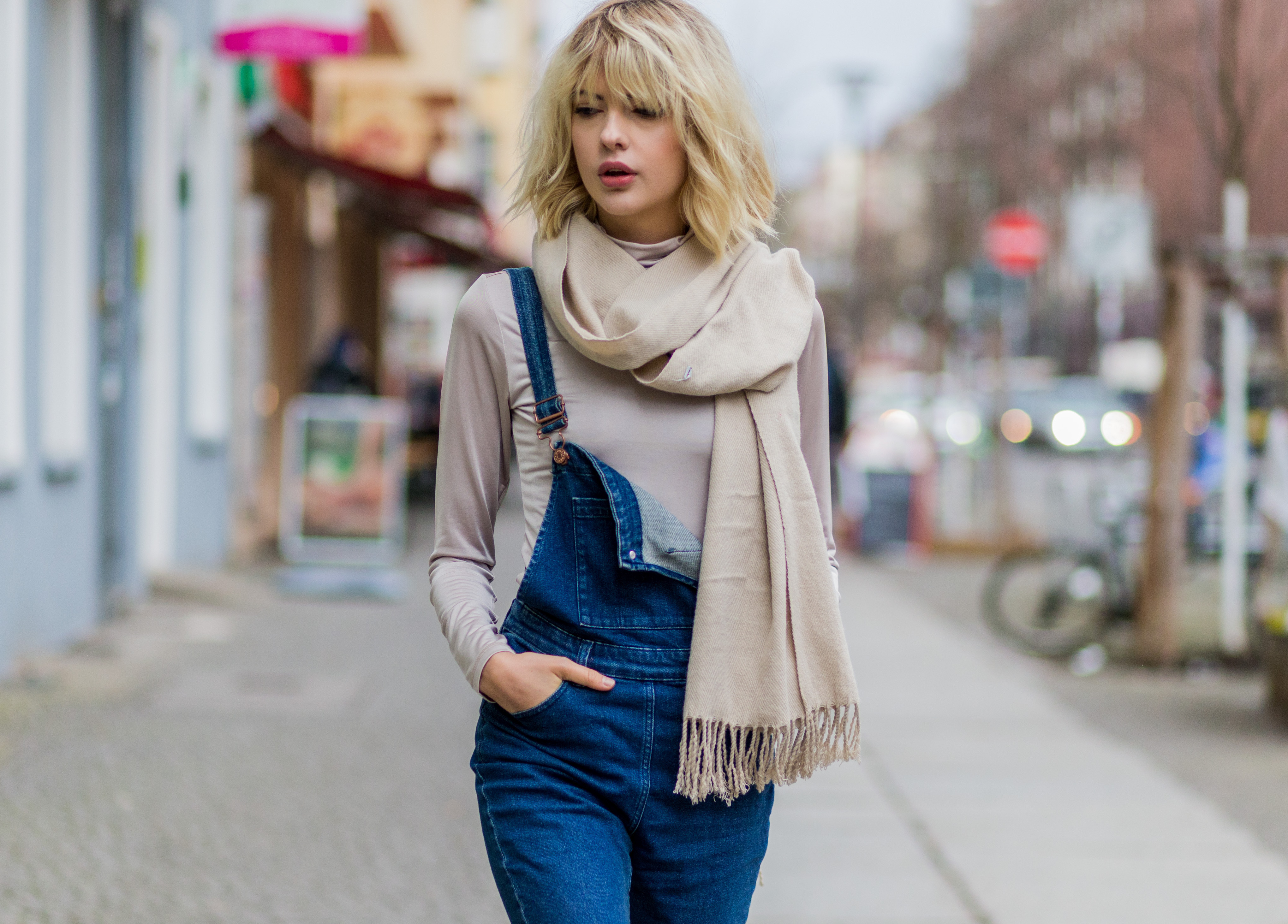 Fashion blogger Ebba Zingmark wearing dark denim overalls, a white tee shirt, and a camel-colored scarf outside