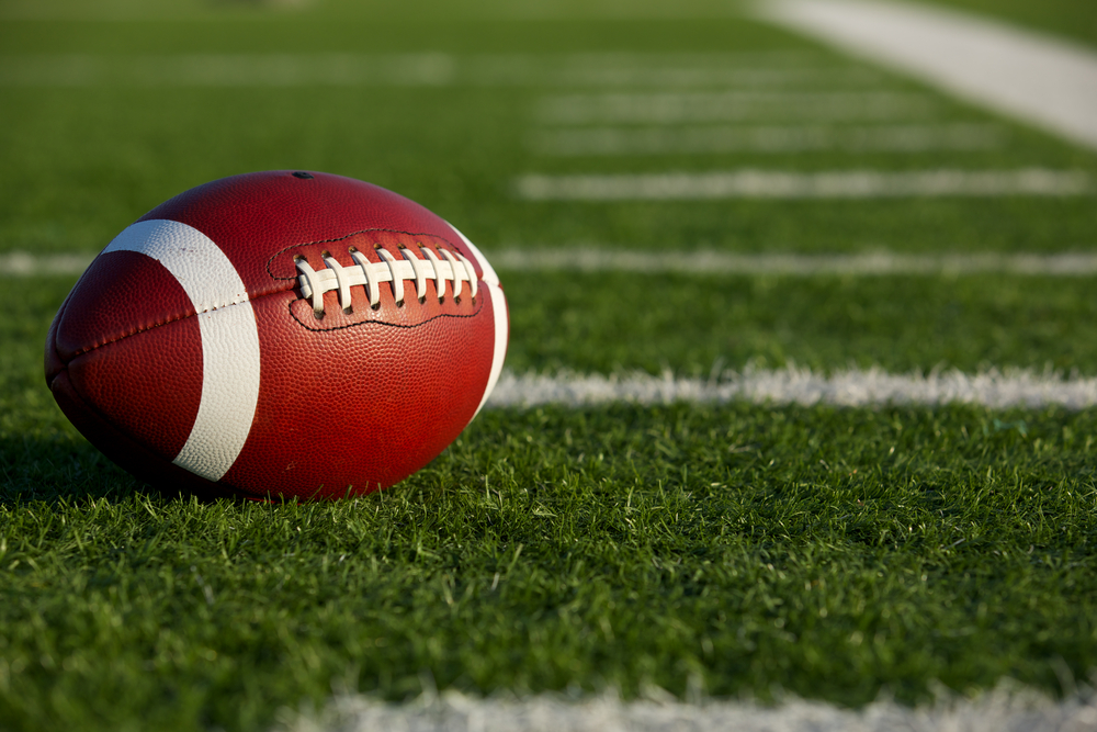 A stock photograph of a football sitting on a football field