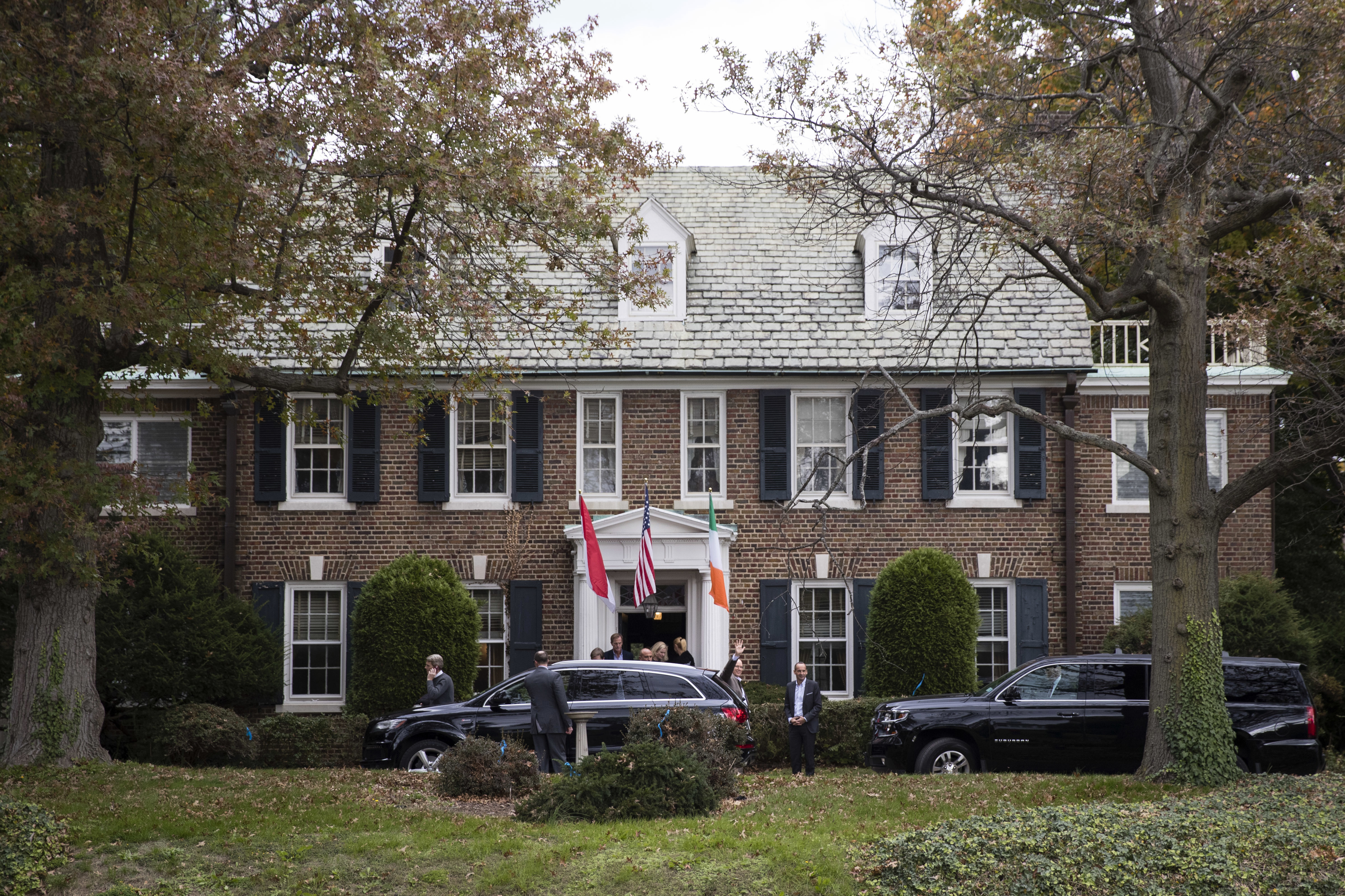 A stately brick colonial with the flags of Monaco hanging out front.