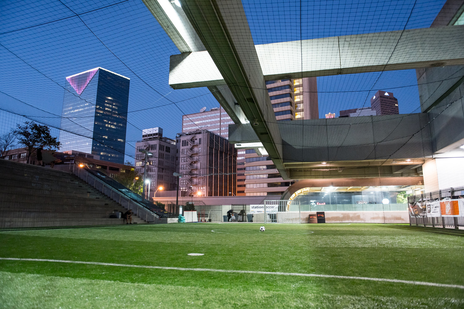 A small soccer field surrounded by the brutalist train station, with the downtown skyline beyond.