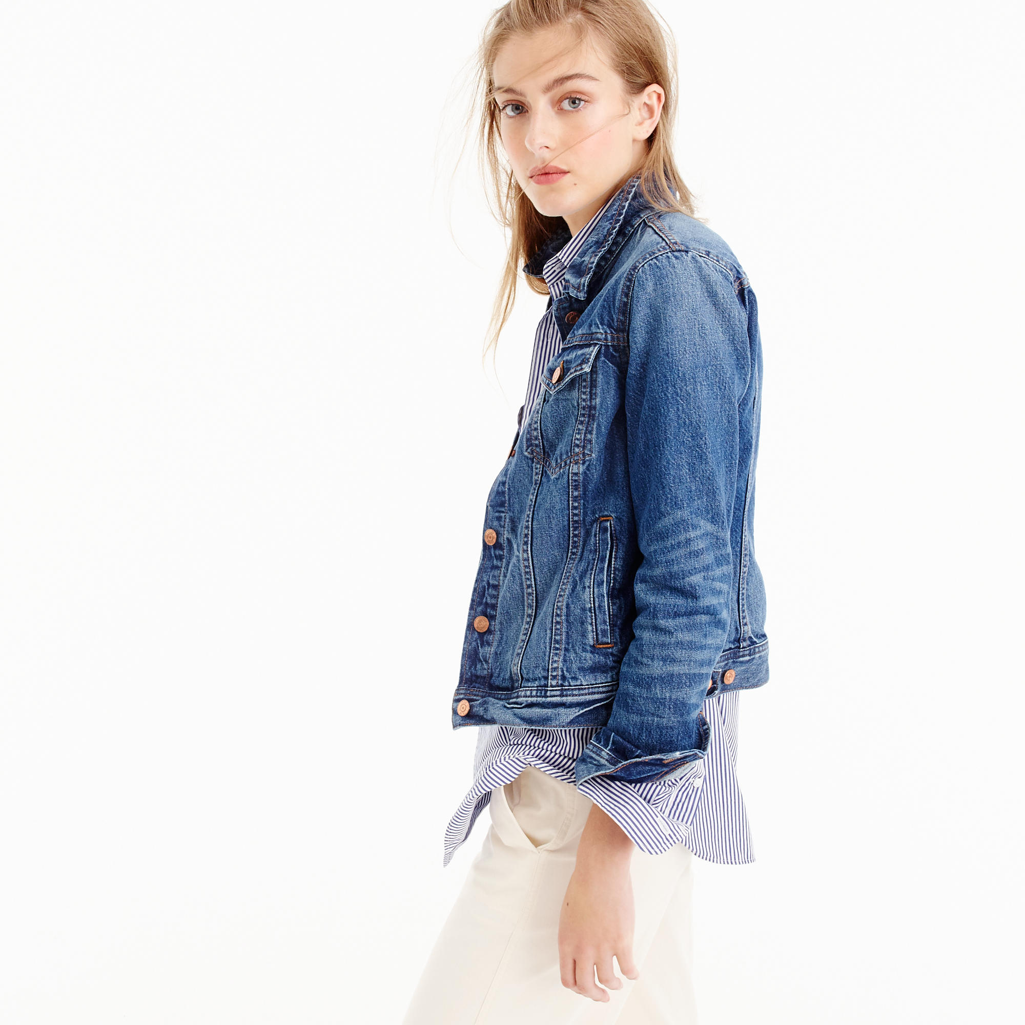 A model wearing a J.Crew denim jacket and white pants