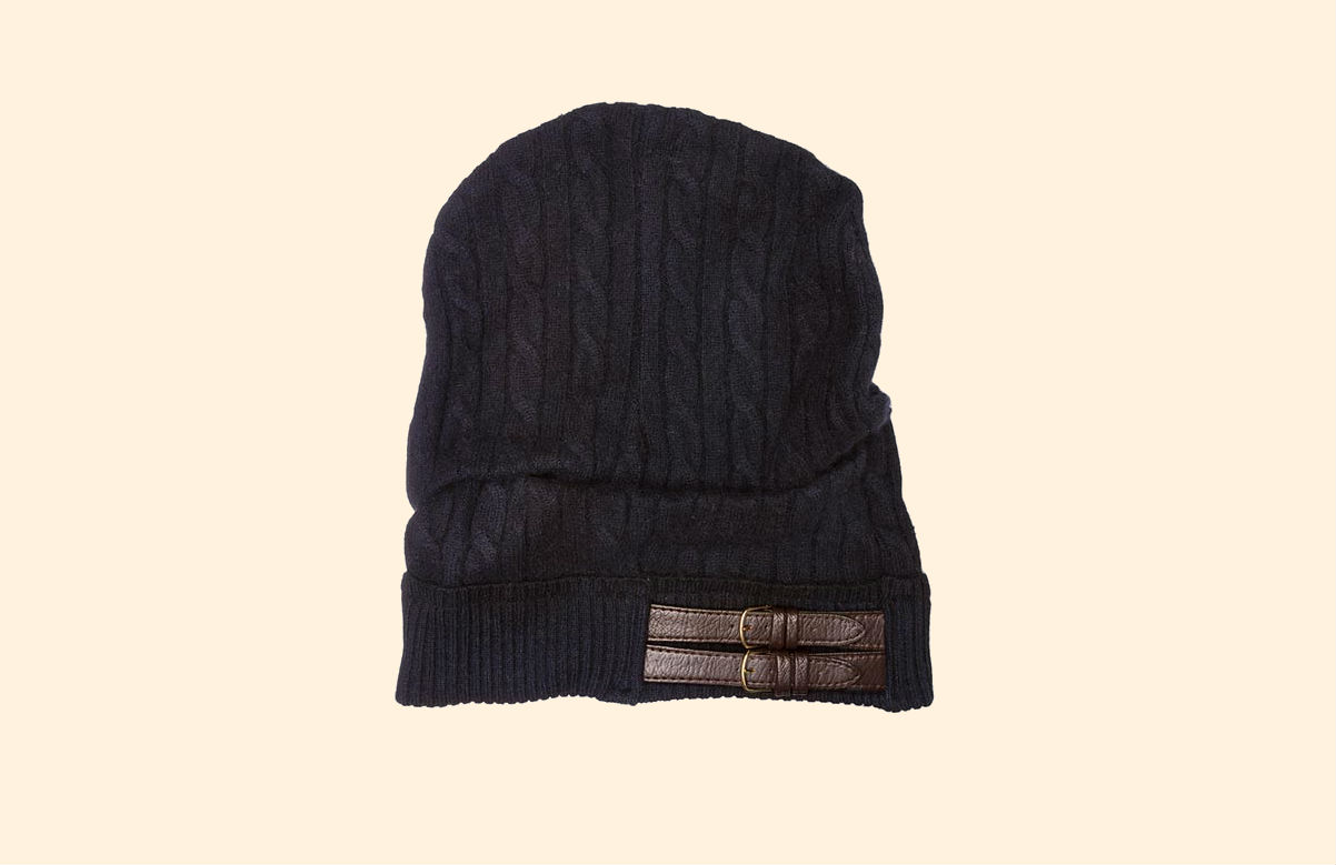 A navy Galadriel Mattei knit hat with two buckles across the side