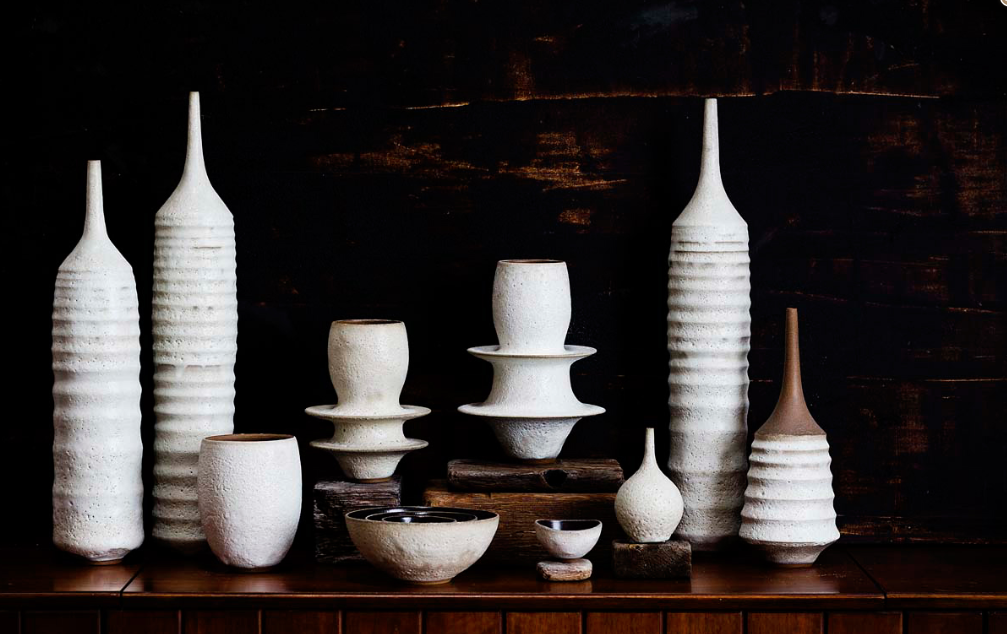 Various white and ivory ceramic objects on a wooden surface.