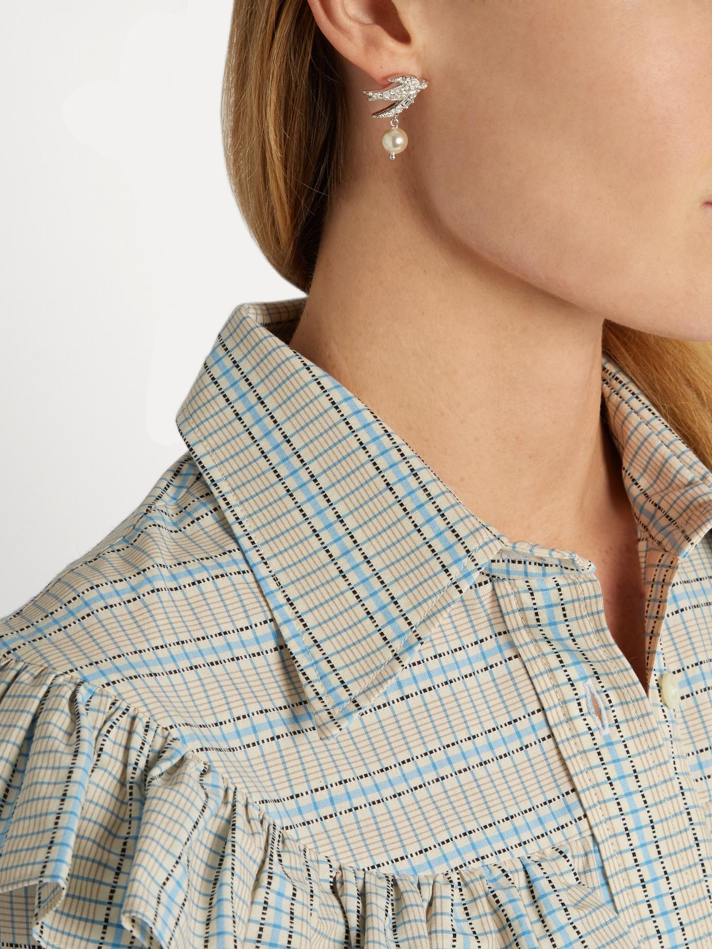 A woman wearing Miu Miu SwallowCrystal Earringsand a plaid shirt with ruffles