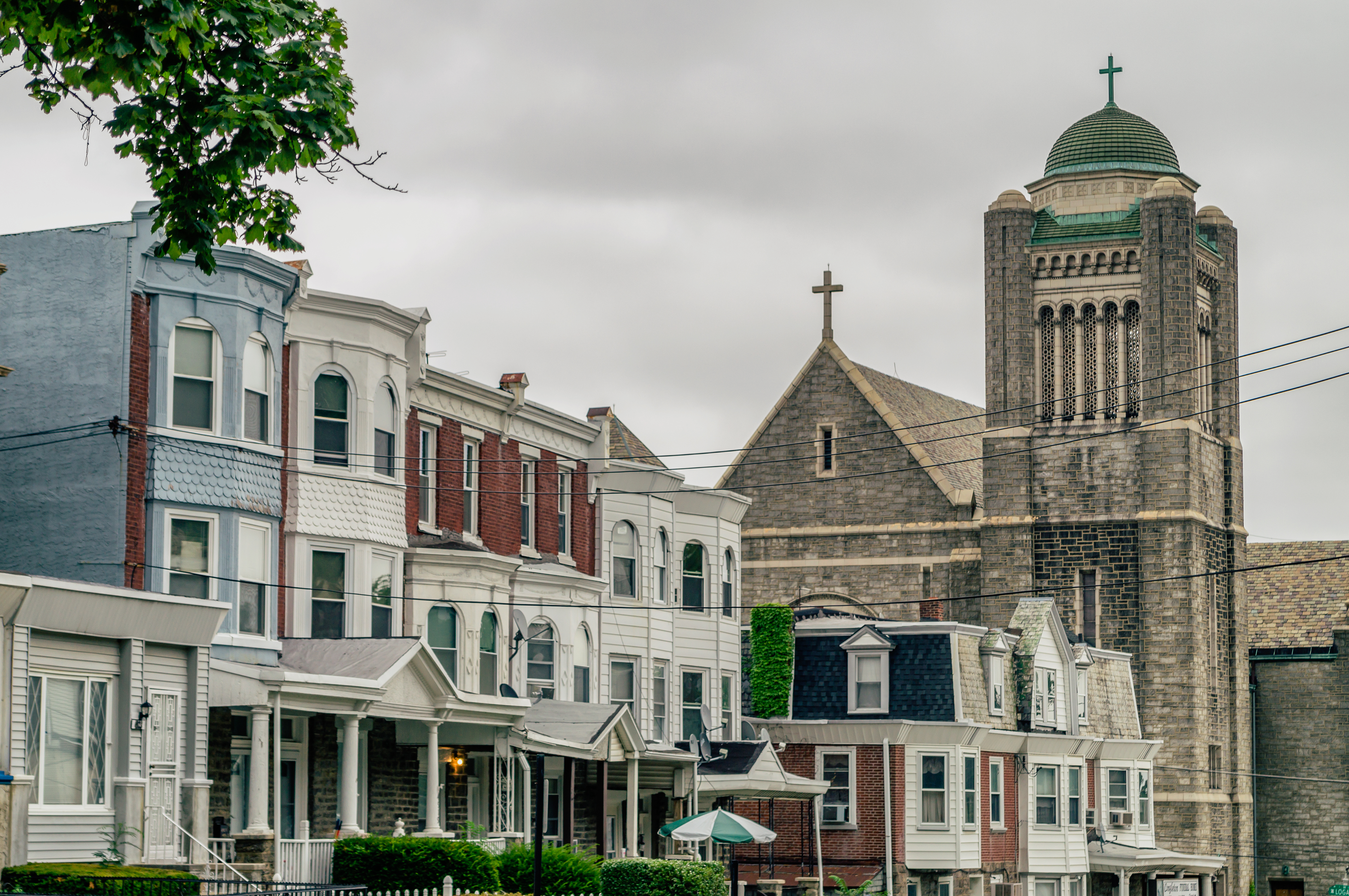 The tops of a rowhomes with a church in the background.