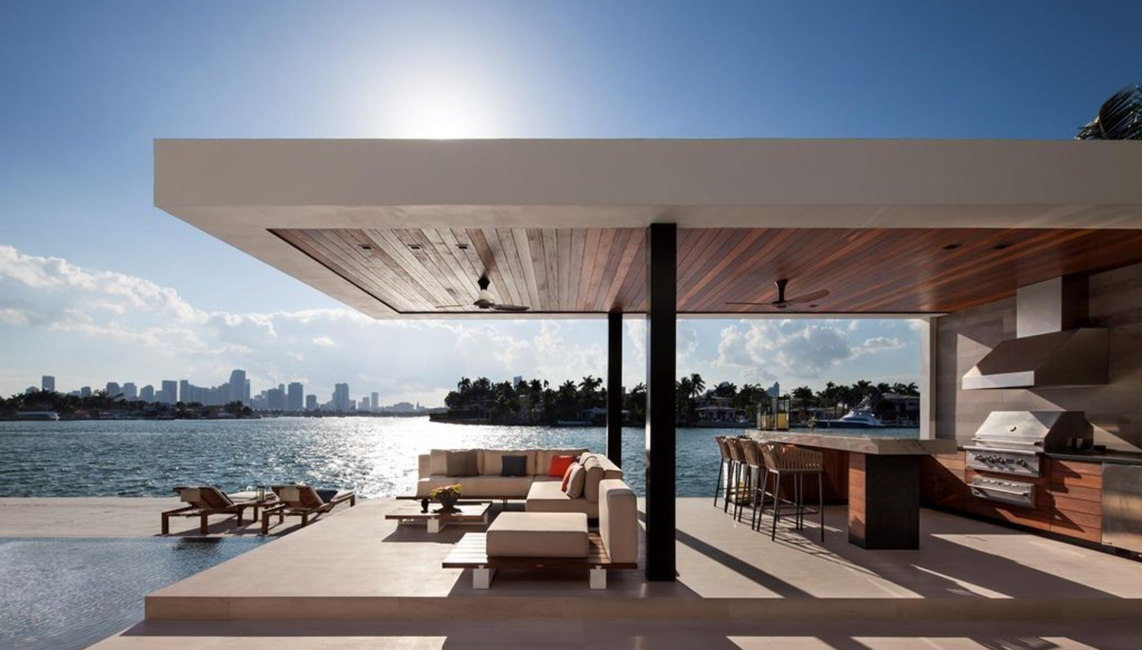 Backyard area of a waterfront home in miami beach with a modern outdoor kitchen overlooking the bay