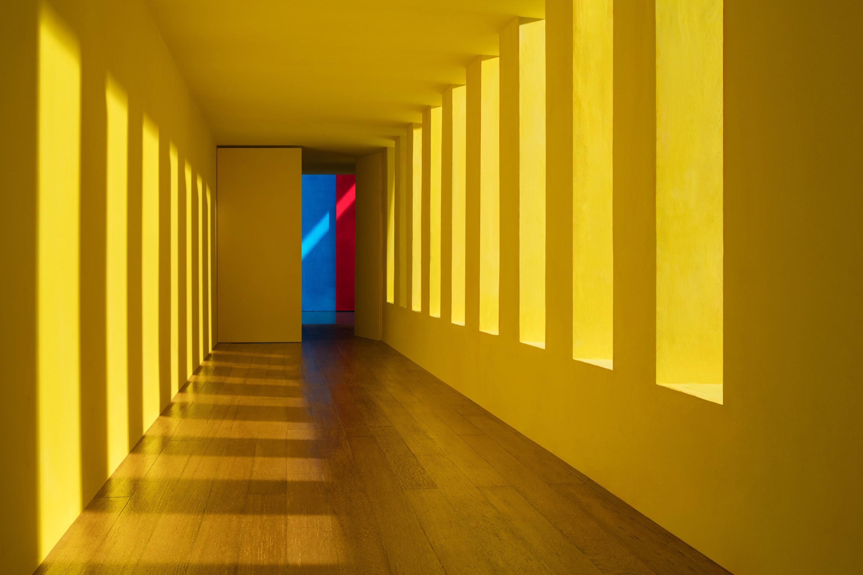 Interior shot of a yellow corridor with pale wood floors and window cutouts through which light comes through and casts shadows on the opposite wall. At the end of the corridor are a bright blue and red walls.