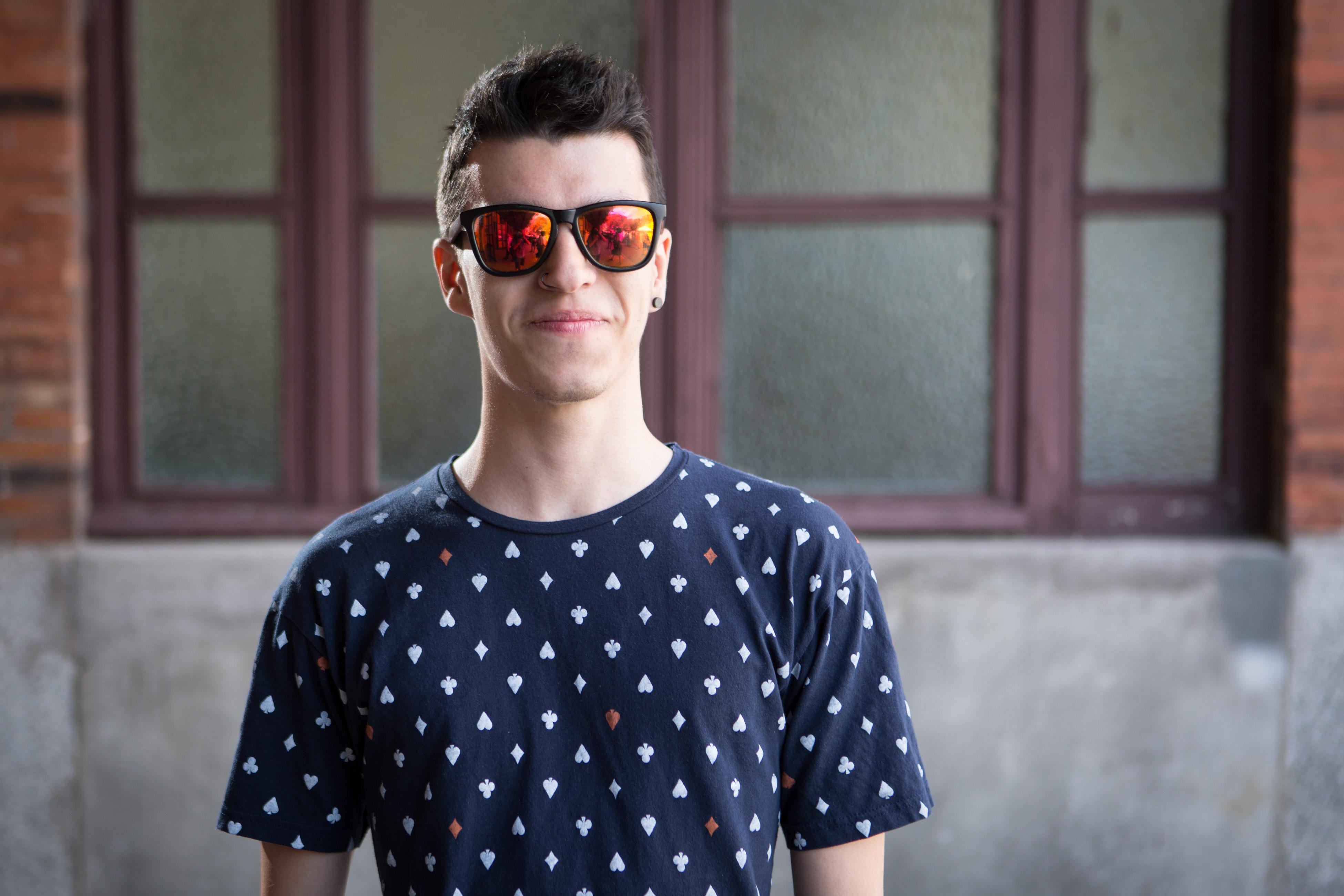 A man in an indigo shirt and sunglasses.