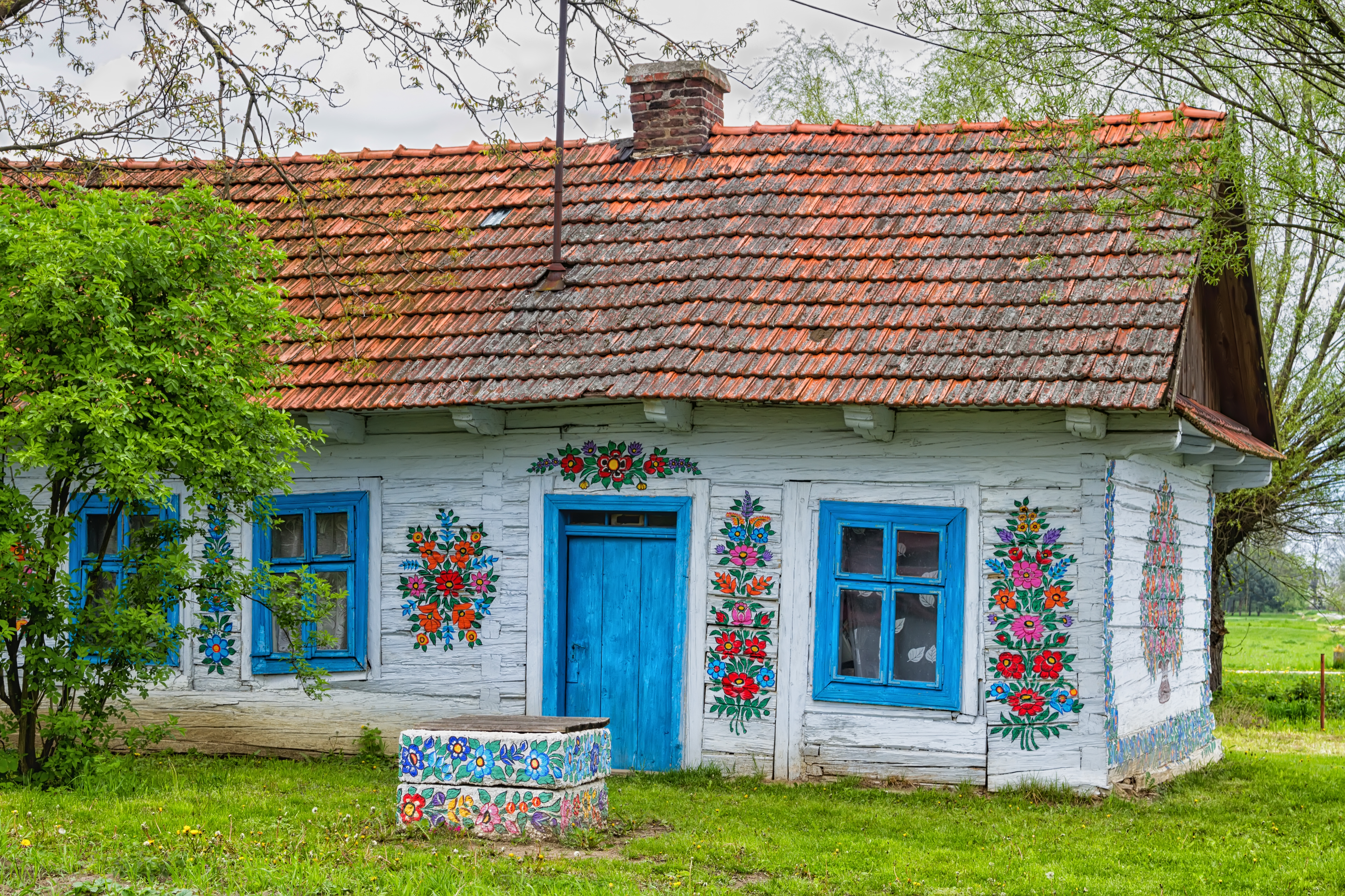 The exterior of a traditional house in Poland. The roof is red, the shutters and door are blue, and there are decorative flowers painted on the white walls.