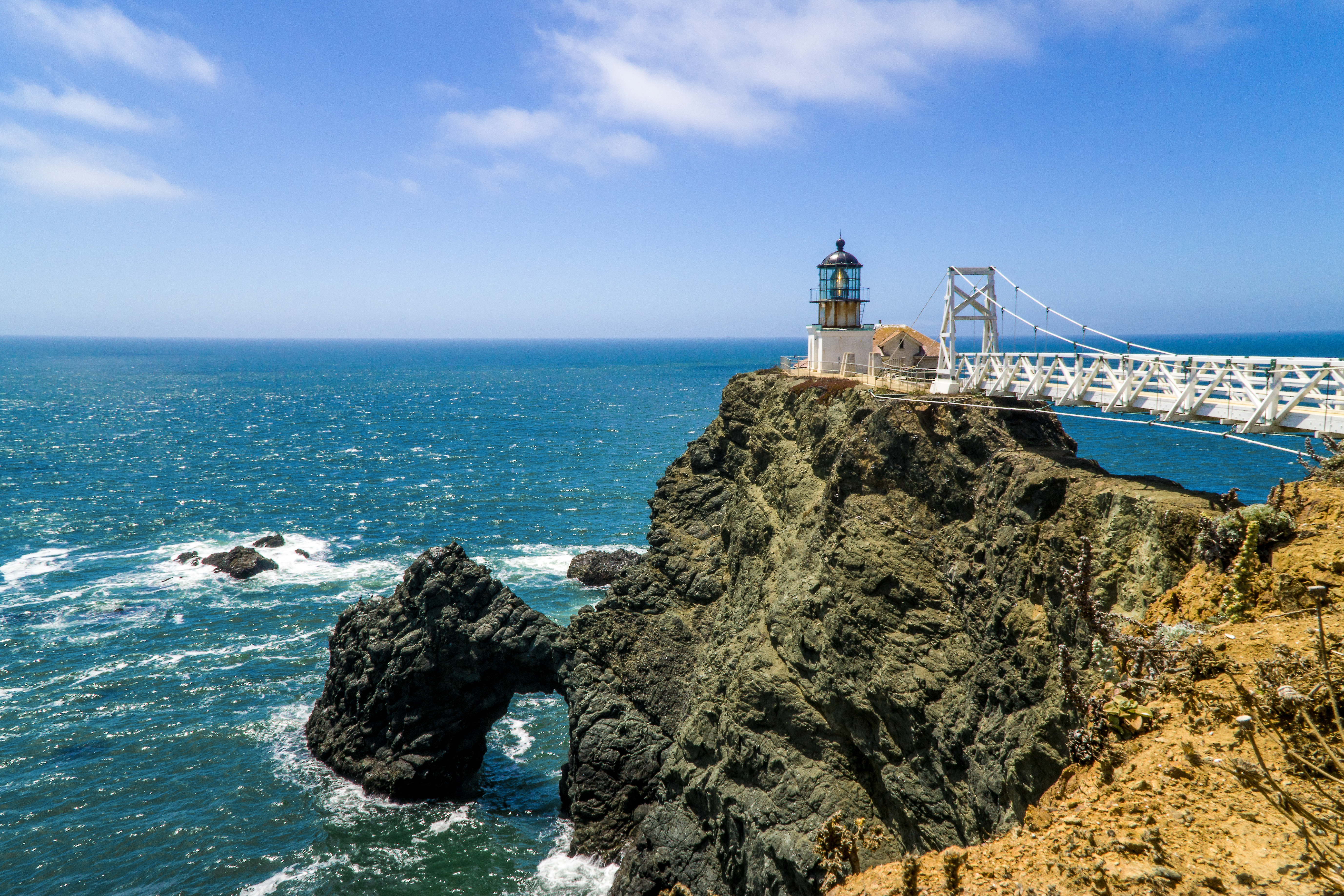 A rocky cliff adjacent to a body of water. Point Bonita Lighthouse is on the cliff. A bridge spans from land to the area of the cliff that the light house is on.
