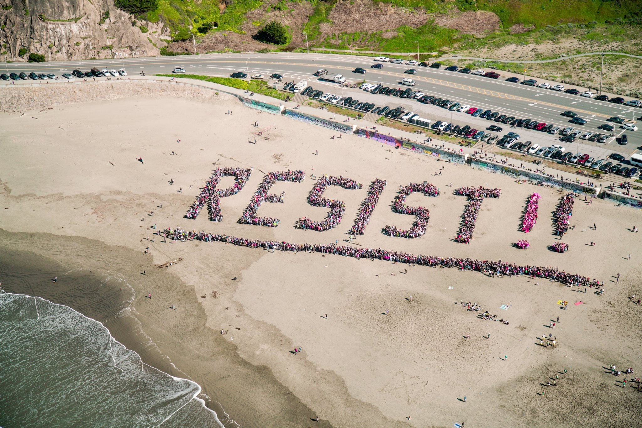 """thousands of people spelling out """"resist!"""" on the sands of ocean beach in san francisco."""