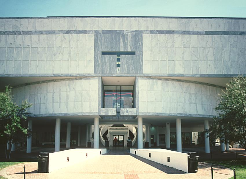 A three-story postmodern white marble building, with the two main floors elevated above a plaza with columns, and a grand double stair leading up.