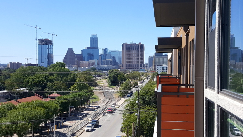 Balcony with view of downtown Austin to the west and railroad tracks, trees below