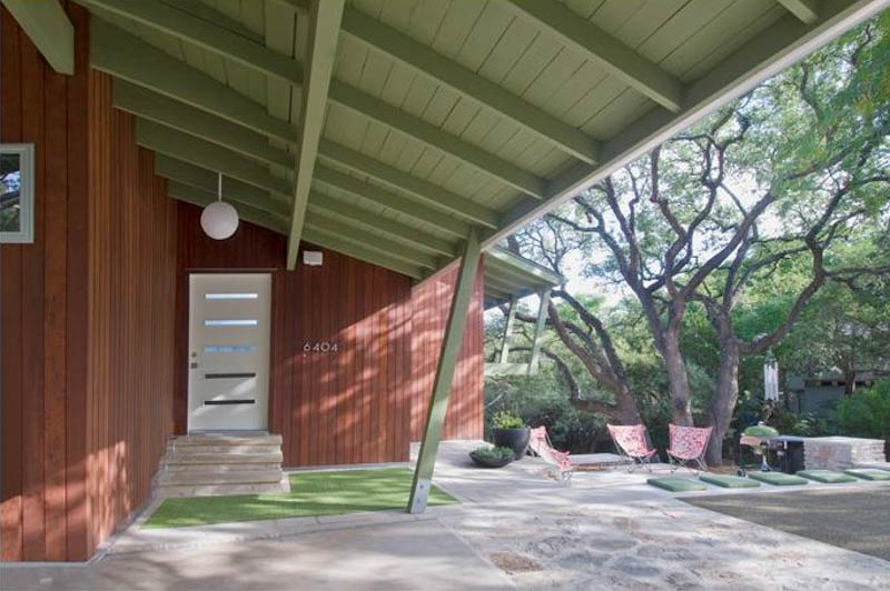 Midcentury-style home front porch entrance with angled roof painted light green and red wooden walls, white door, globe light,