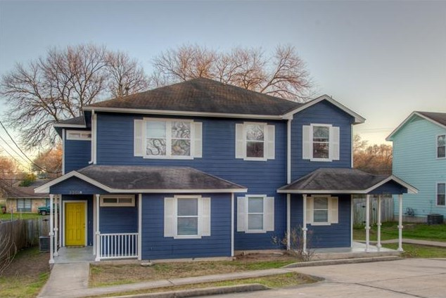 Large 2001 two story duplex painted dark blue with white shutters