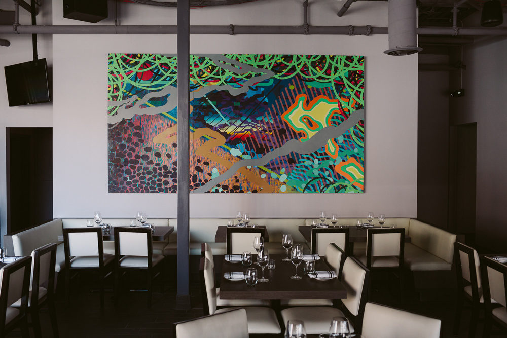 A neon painting hangs on a white wall in the dining room at Bistro 82.
