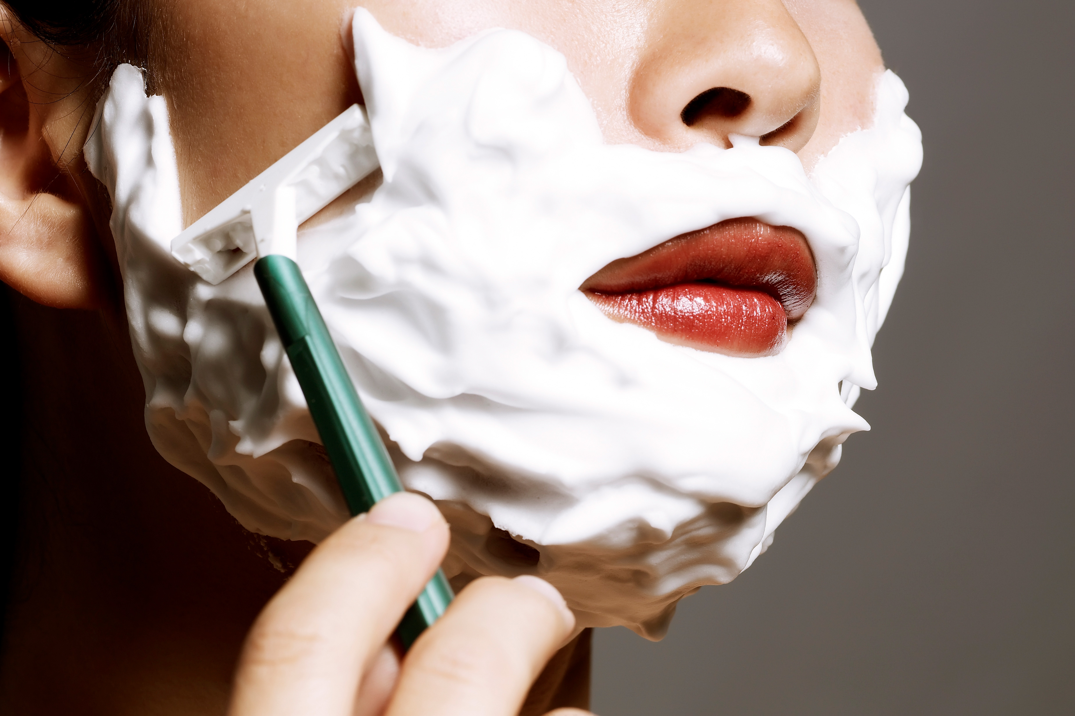 Lower half of a woman's face is covered in shaving cream as she uses a razor to shave her face
