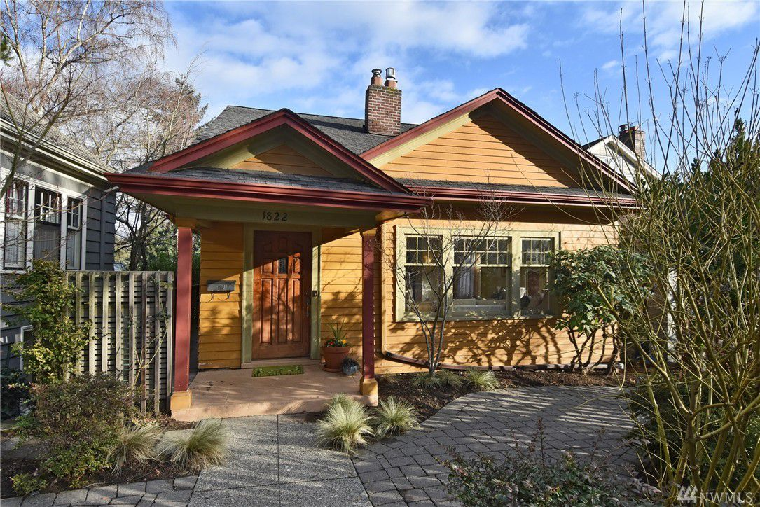 A small, goldenrod-colored 1918 home with a deep red trim.