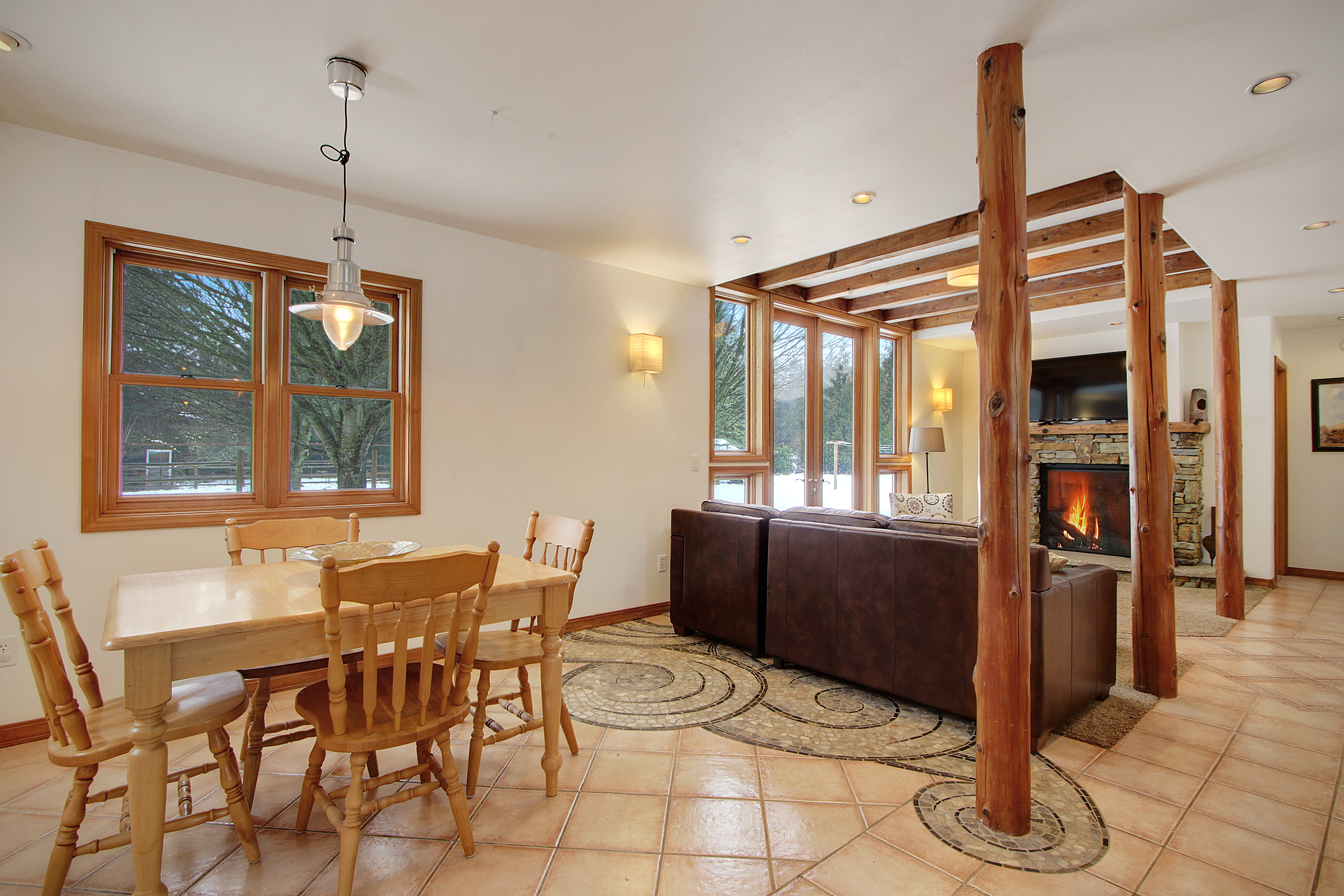 An open living room and dining area with exposed beams and a tile wave motif on the floor