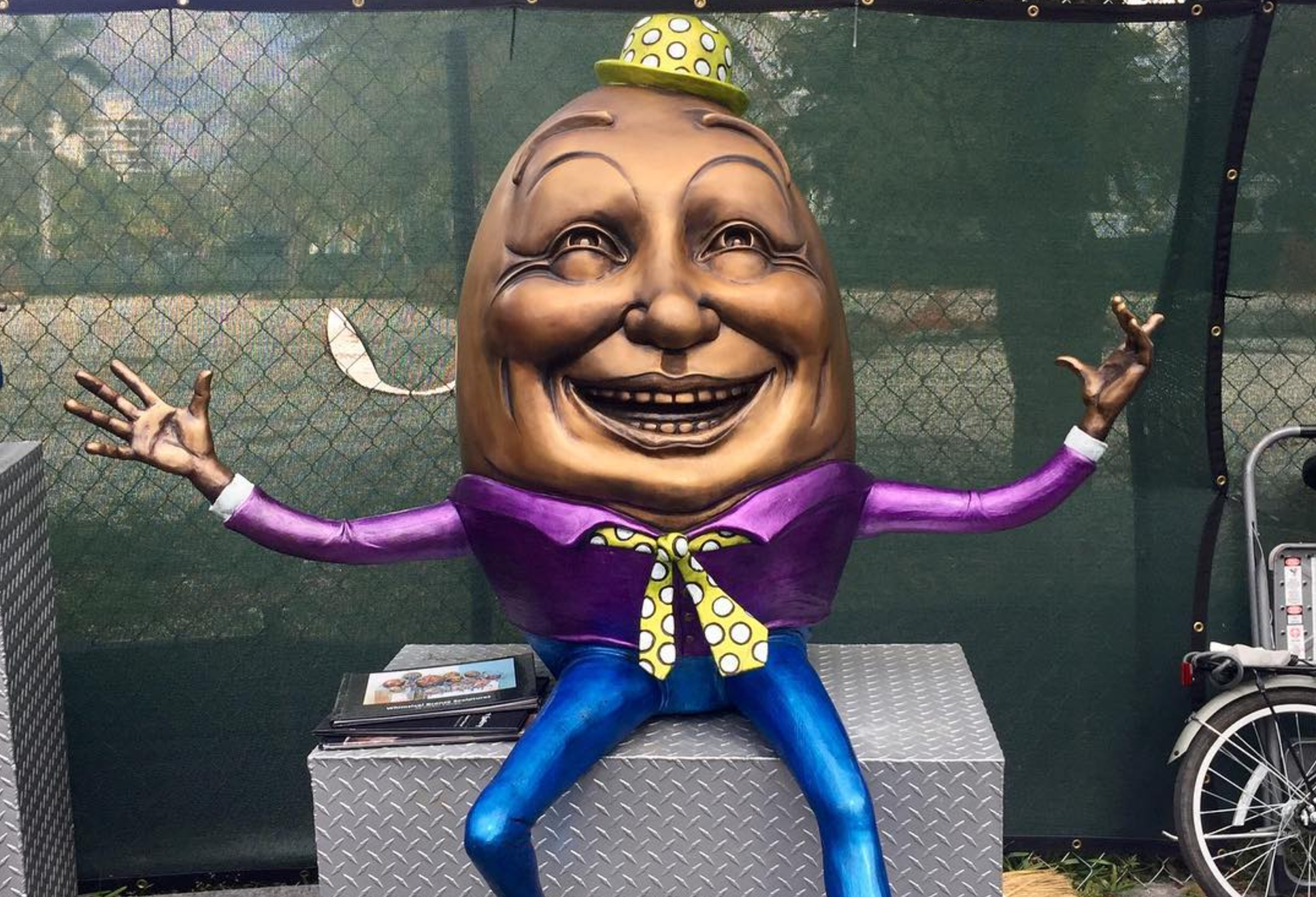 An art piece at the Coconut Grove Arts Festival, featuring a bronze sculpture of humpty dumpty