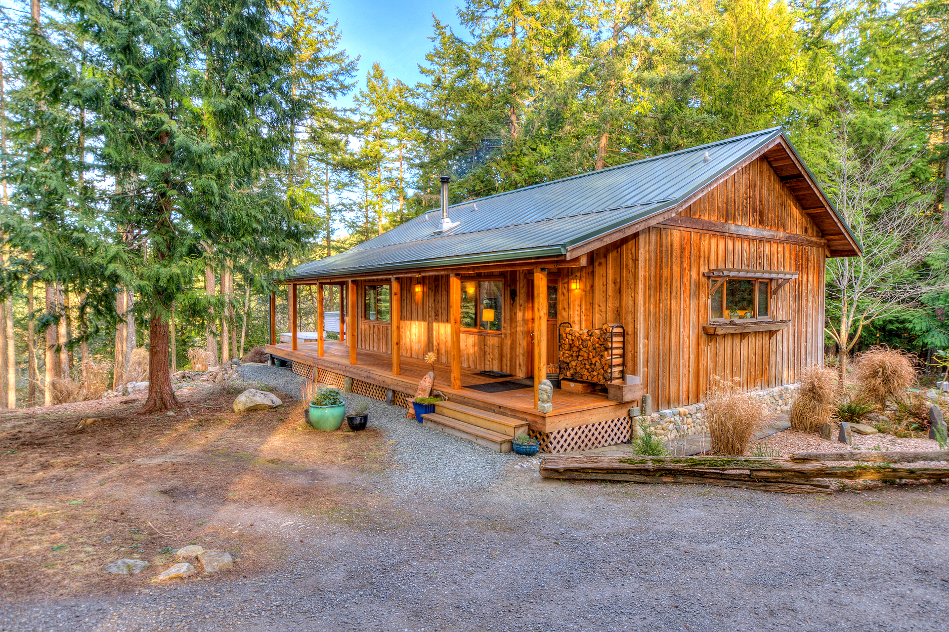 A wooden cabin in the woods with a large porch