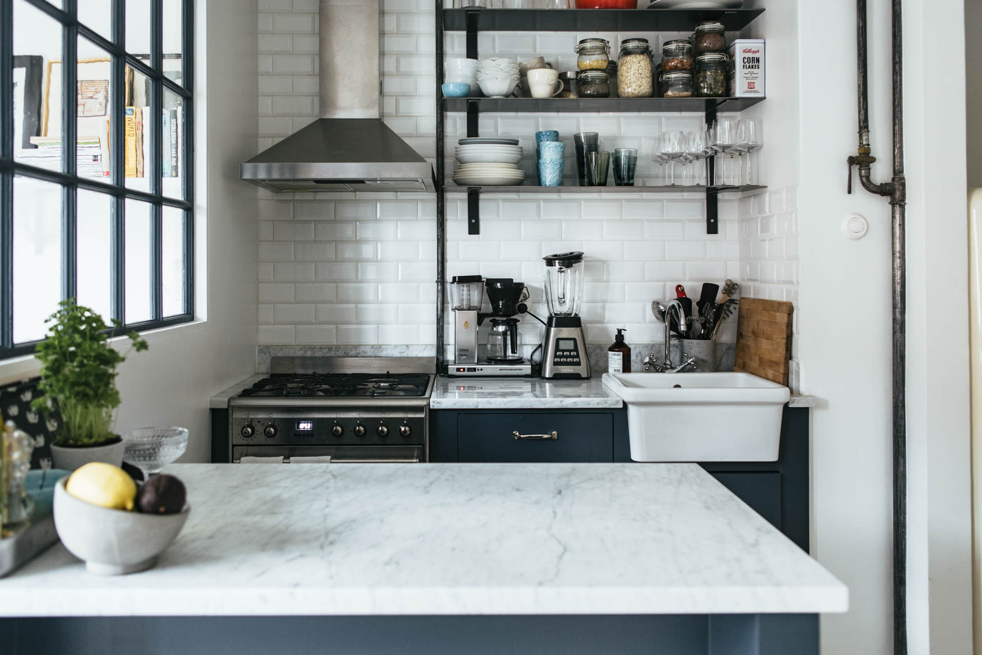 Shot of small kitchen with white subway tile back splash, marble countertops, farmhouse sink, and stainless steel stove with oversized exhaust hood.