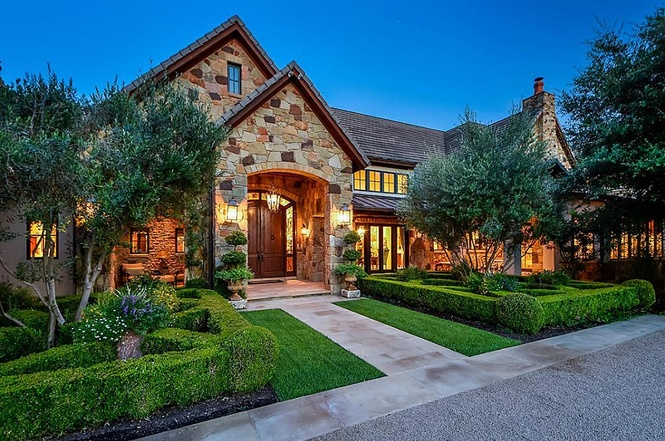 Exterior of traditional stone home with peaked entryway roof, manicured shrubbery