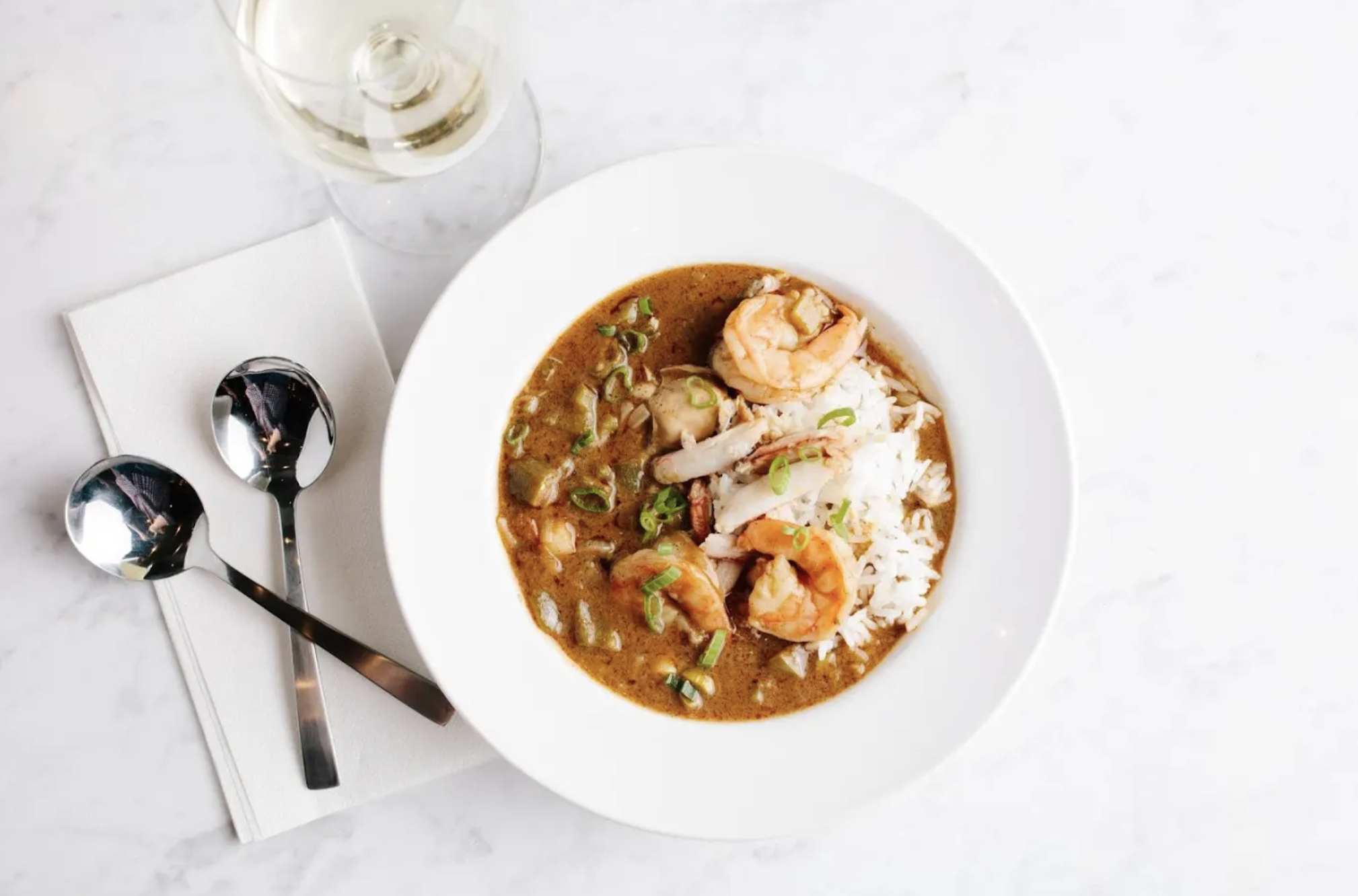 A white bowl filled with gumbo with rice and big pink shrimp on top