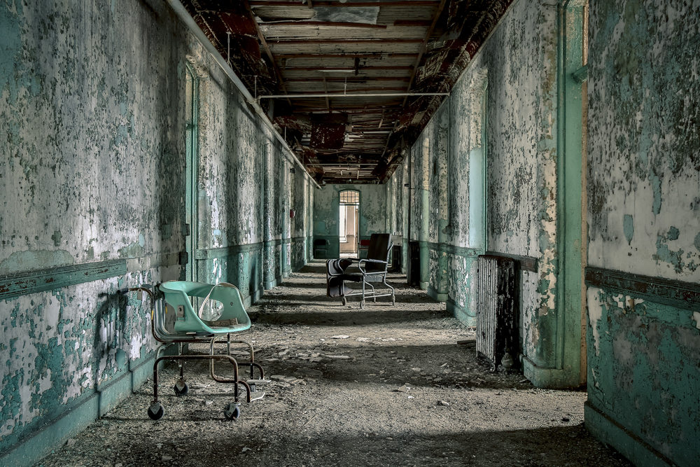 Interior shot of an abandoned and deteriorating hallway with chipped paint and rusty chairs.