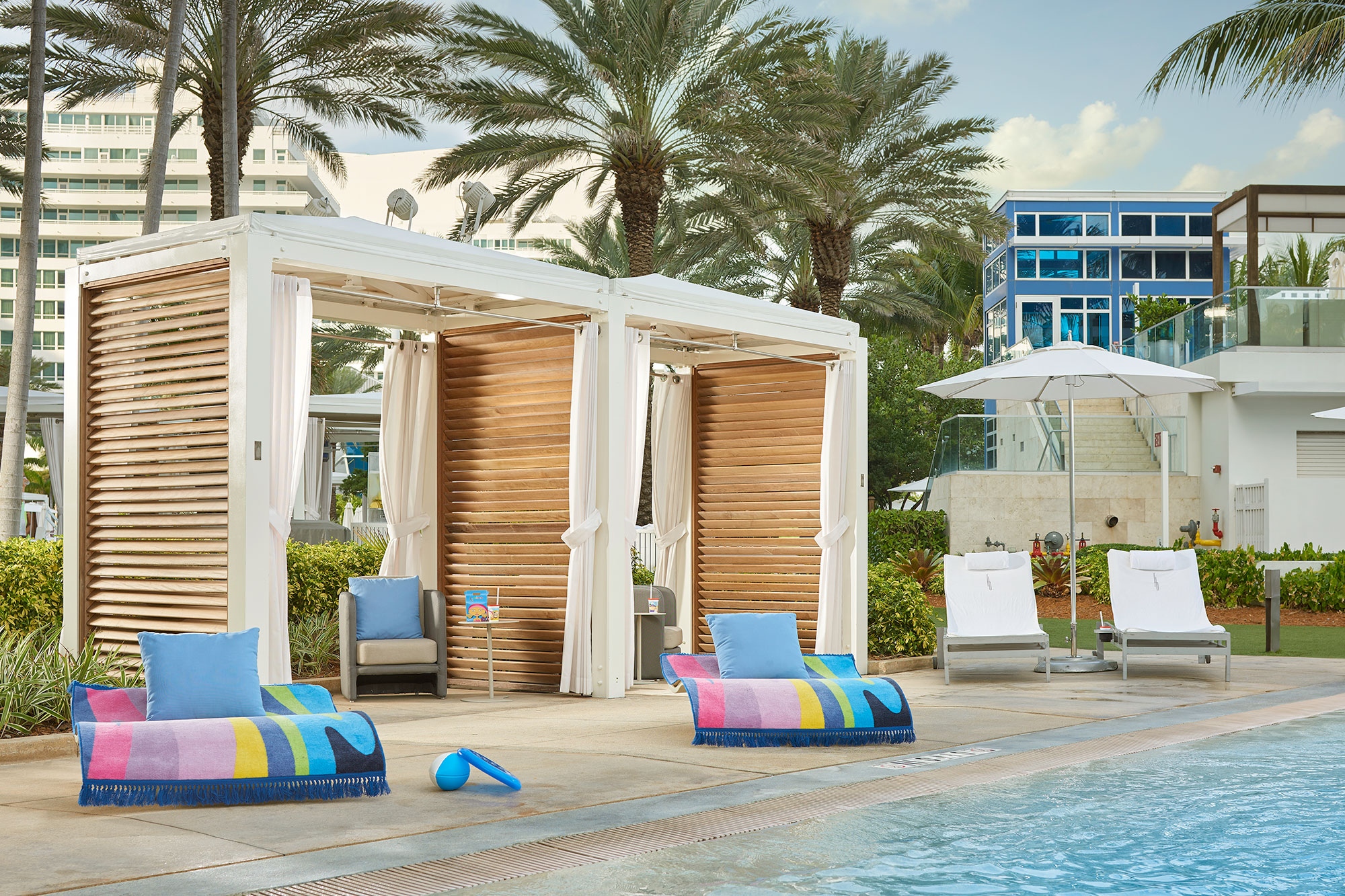 A poolside cabana at FontainebleauMiami Beach with colorful seating and a tropical modern feel