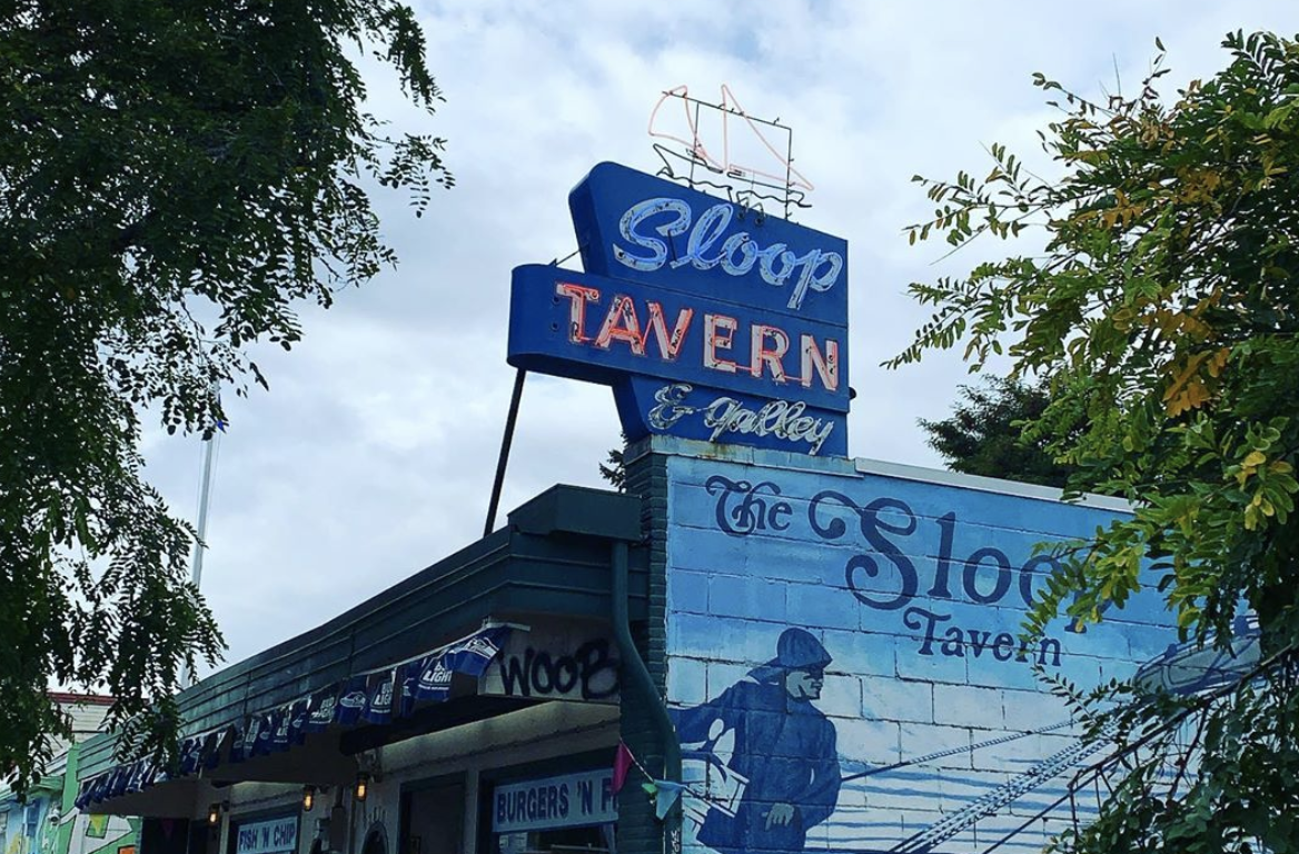 The retro signage outside Sloop Tavern, with a painting of a fisherman on the outside