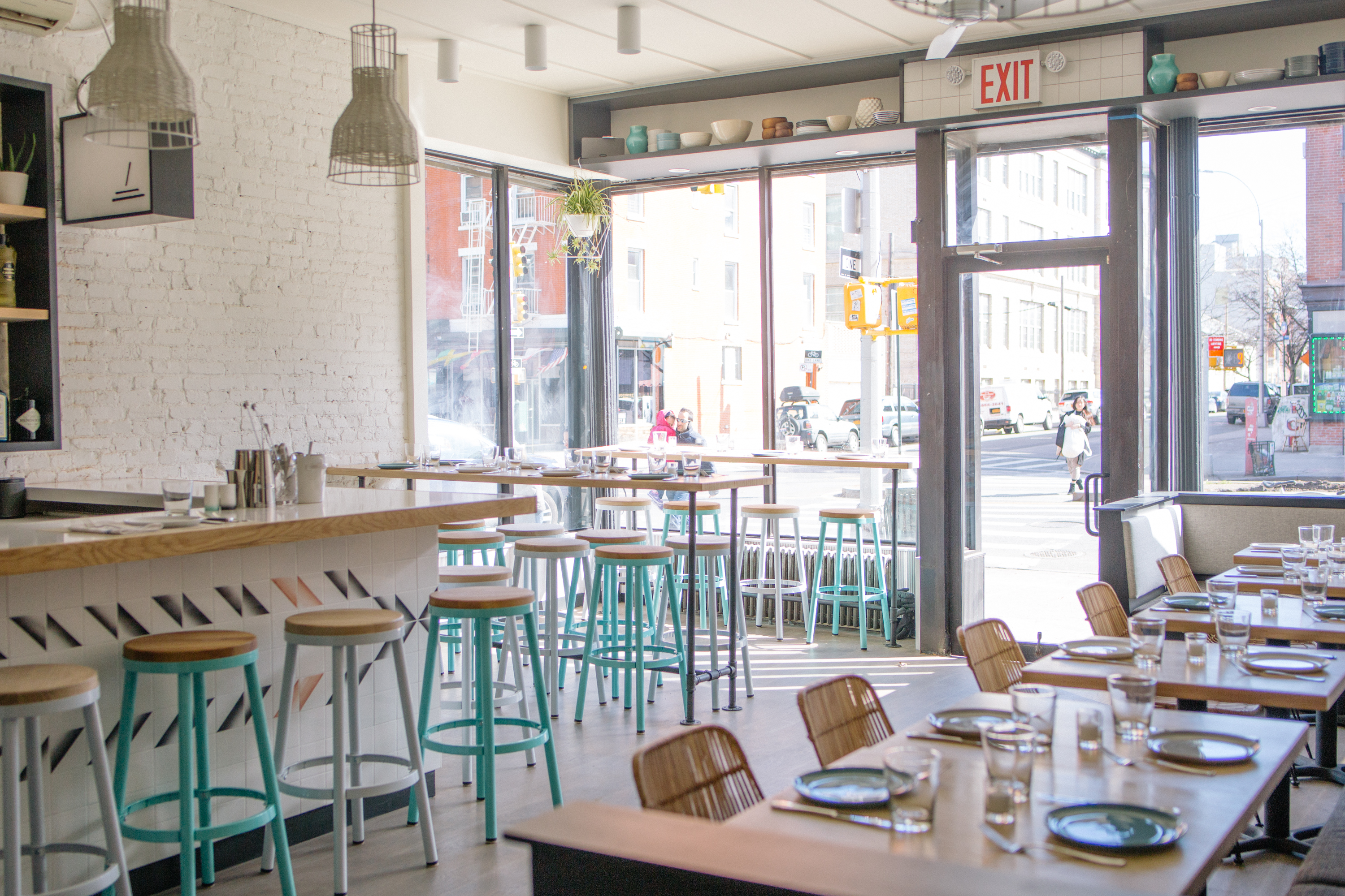 Alta Calidad's dining room has wood tables, turquoise blue stools, big front windows, and brick walls painted white