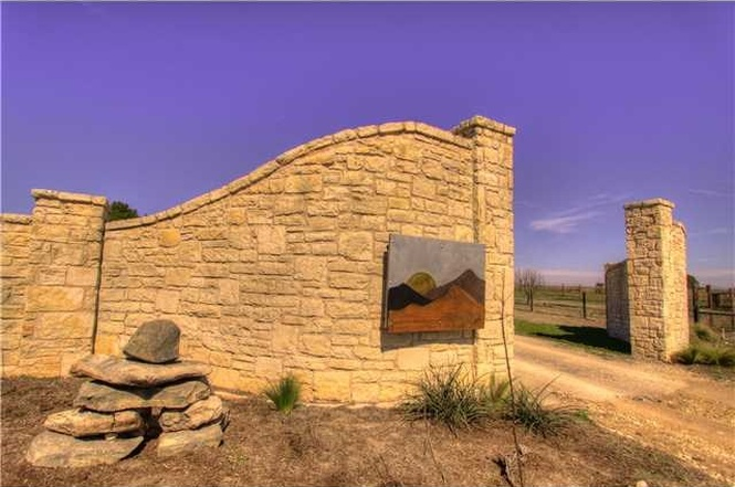 Curved stone gate/ranch entrance and dirt road