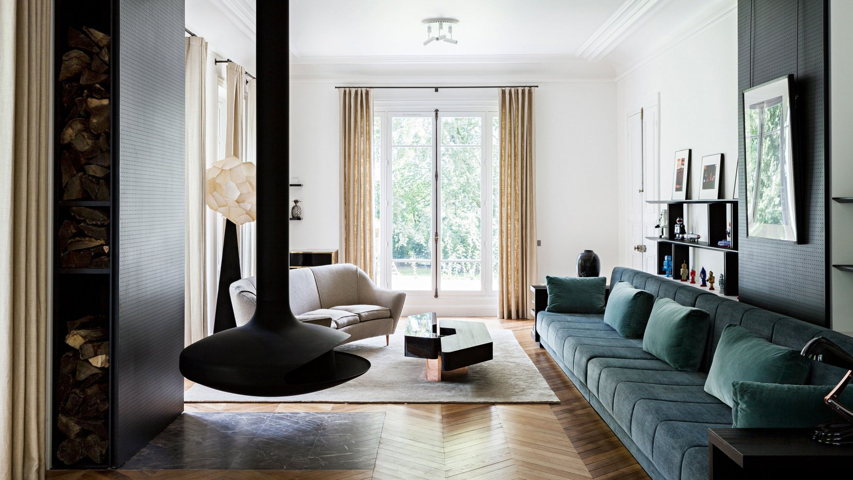 Interior shot of living room with white walls, high ceilings, tall window, parquet floors, floating fireplace, long teal sofa, and other modern pieces of furniture.